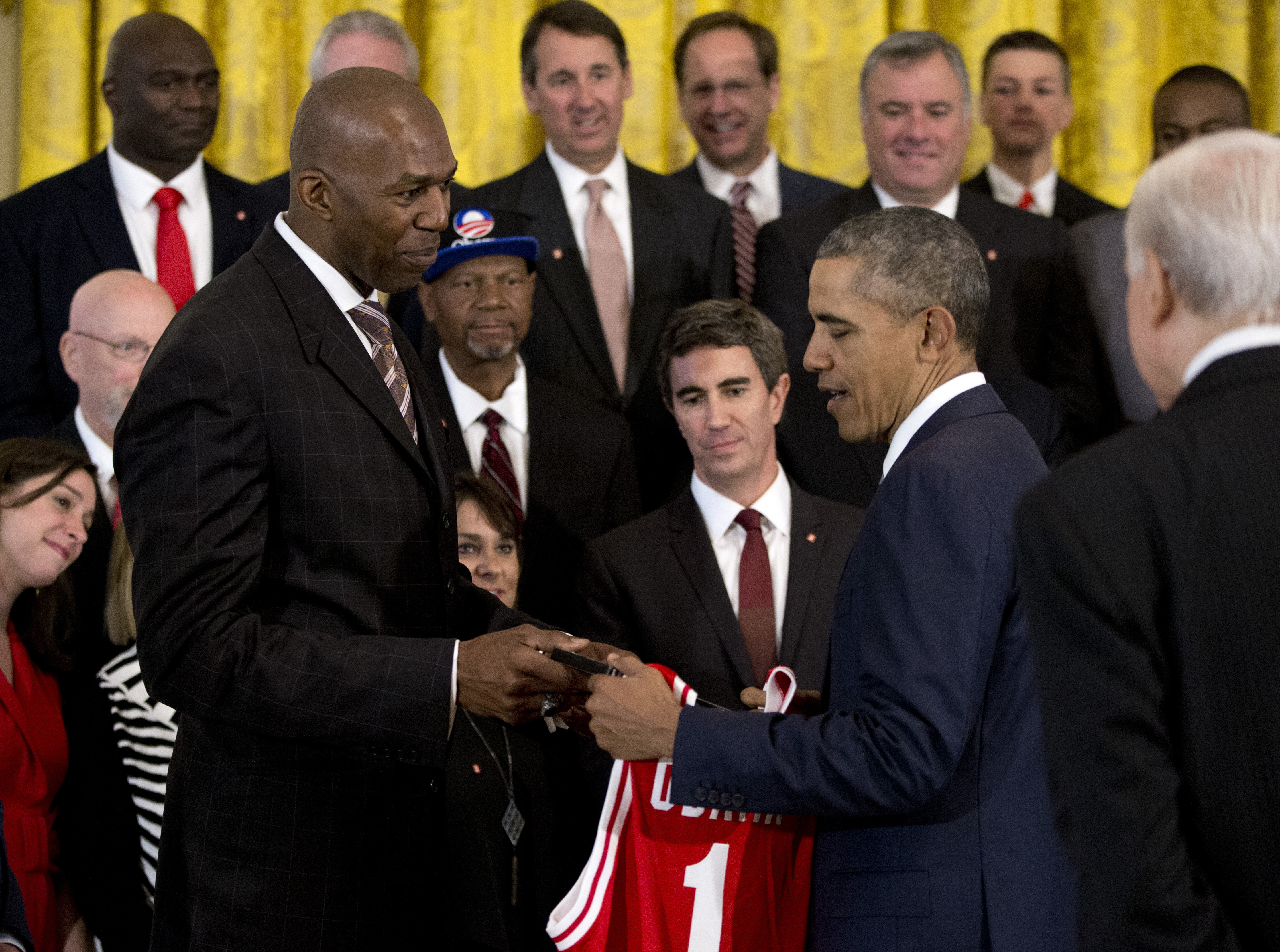 Former North Carolina State Wolfpack basketball, player, retired NBA player Thurl Bailey, gives President Barack Obama a jersey and gift as other members of the 1983 North Carolina State NCAA National Championship basketball watch, Monday, May 9, 2016, in