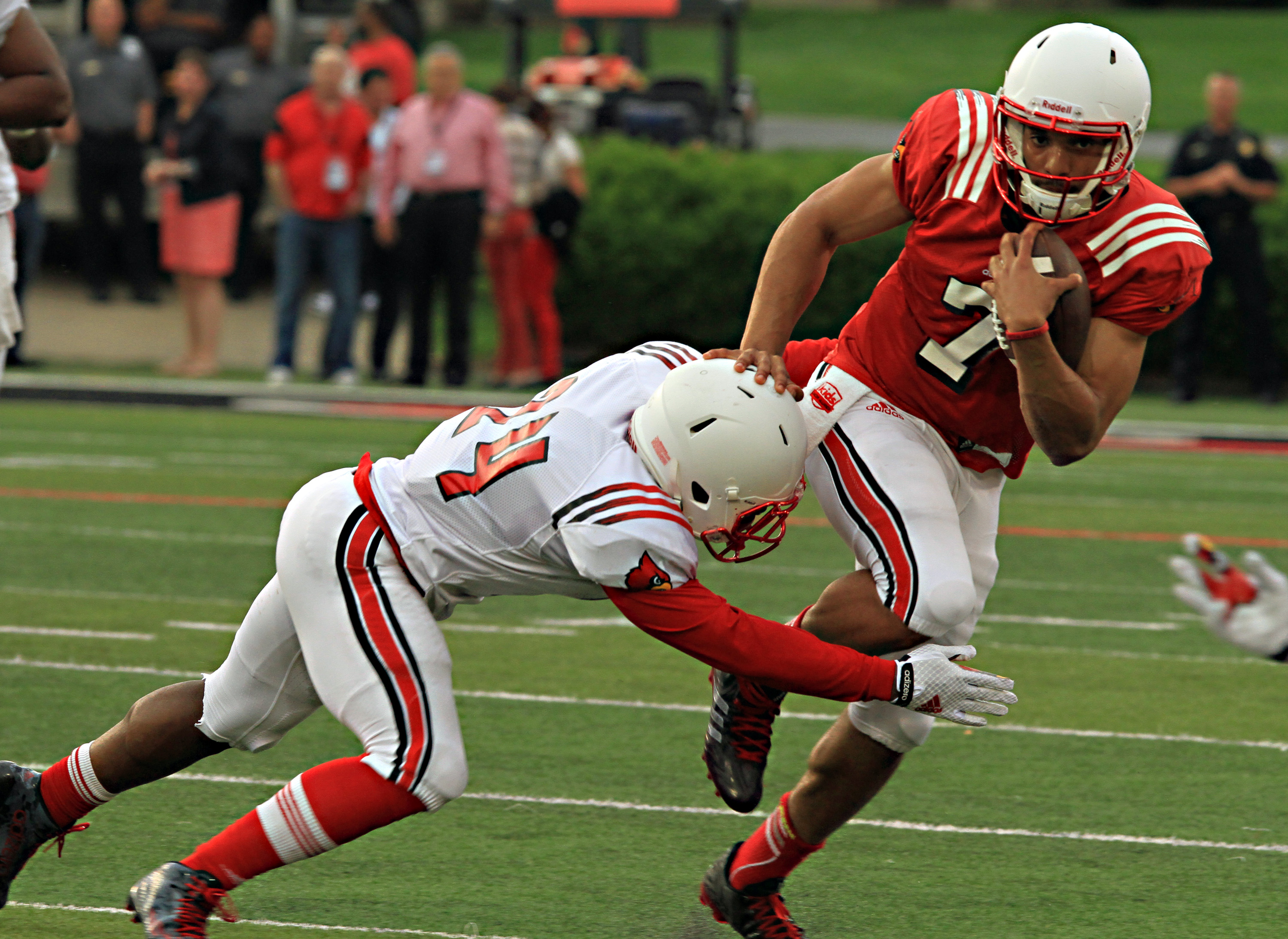 Louisville quarterback Reggi Bonnafon (7) runs through the tackle attempt by safety Zykiesis Cannon (24) in the annual spring football scrimmage game at Cardinal Stadium in Louisville, Ky., Friday, April 17, 2015.  (AP Photo/Garry Jones)