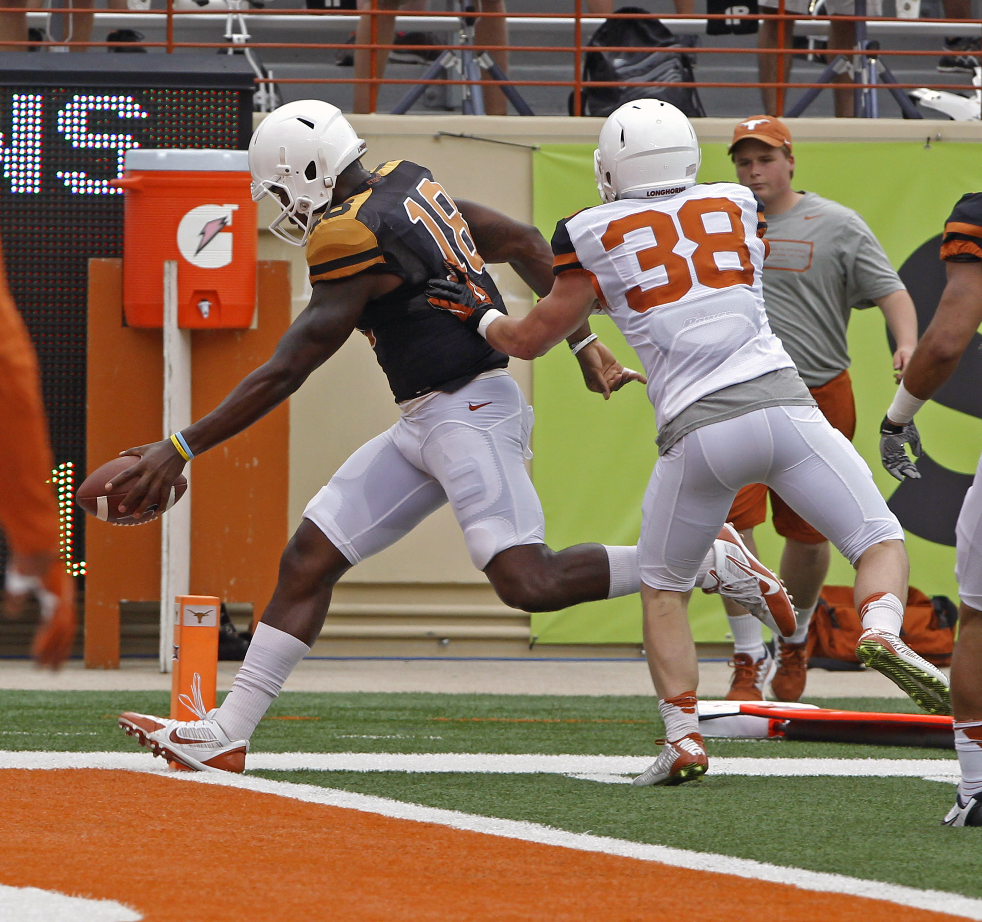 Texas orange quarterback Tyrone Swoopes (18) scores a touchdown against Texas white player Tyler Lee (38) during the first quarter of Texas' Orange and White spring NCAA college football game, Saturday, April 18, 2015, in Austin, Texas. (AP Photo/Michael