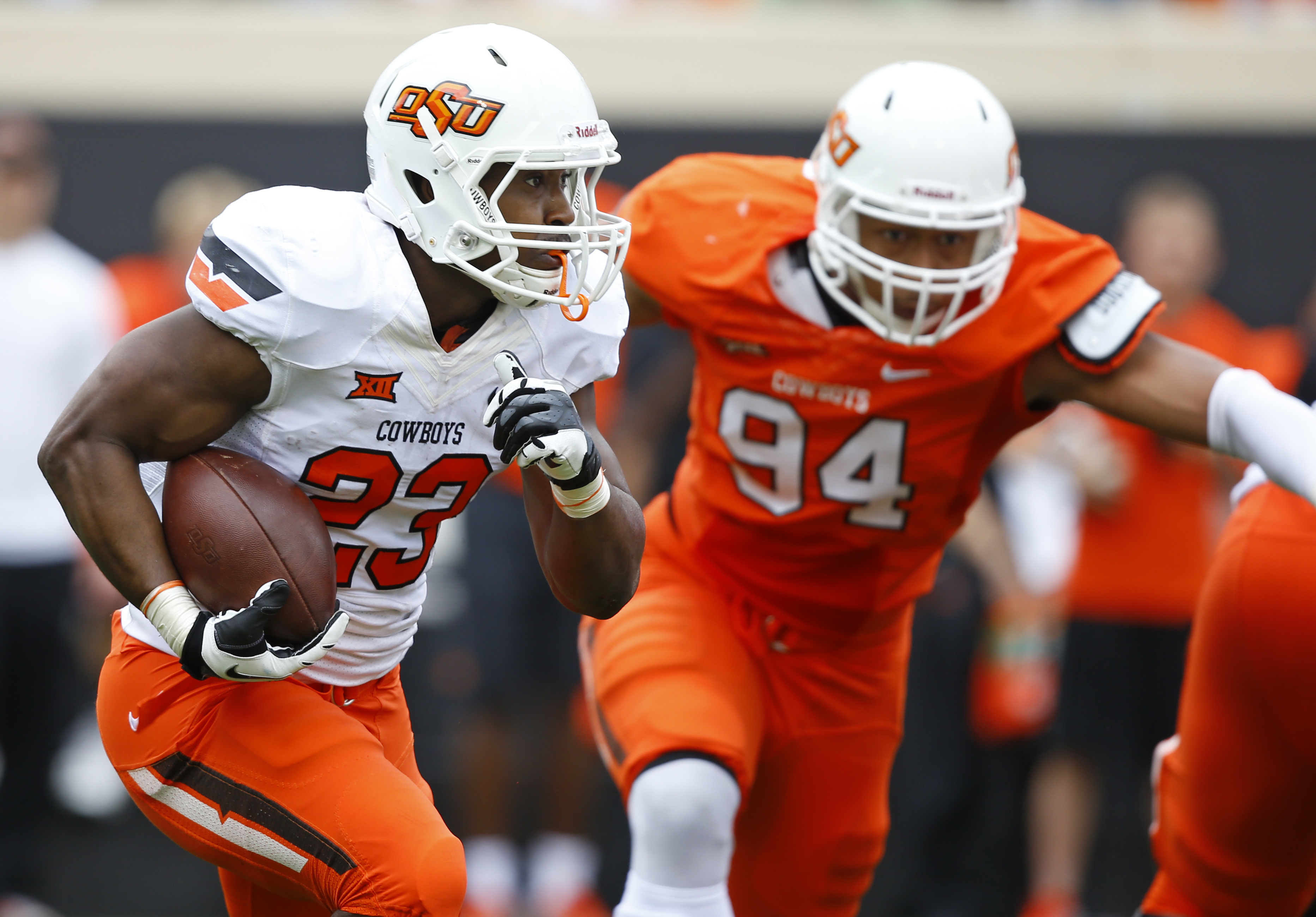 Oklahoma State running back Rennie Childs (23) carries past defender Jordan Brailford (94) in the first half of the Oklahoma State NCAA college spring football game Stillwater, Okla, Saturday, April 18, 2015. (AP Photo/Sue Ogrocki)