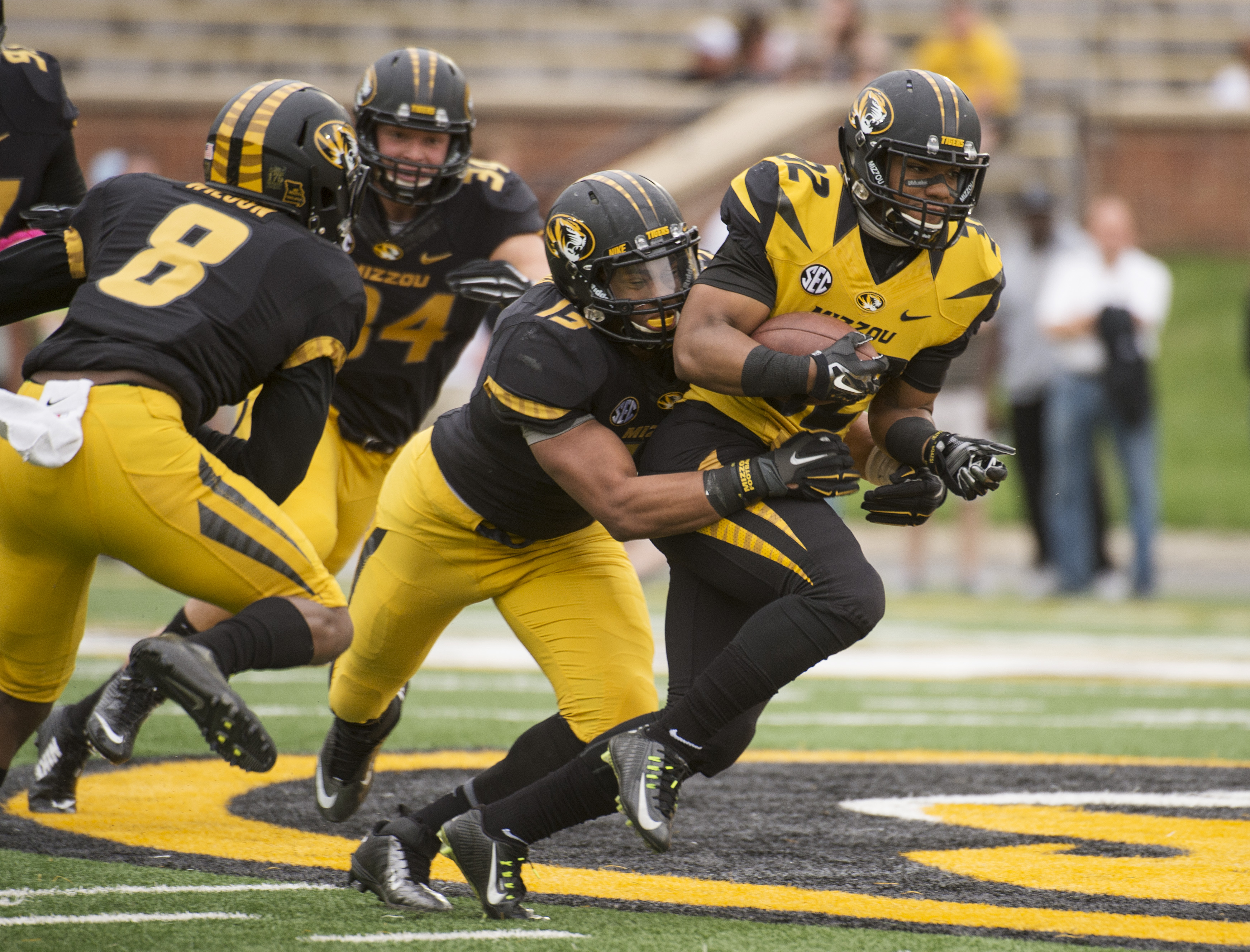 Missouri running back Russell Hansbrough, right, is tackled by Spencer Williams (13) while Thomas Wilson, left, and Joey Burkett (34) move in during an NCAA college spring football game Saturday, April 18, 2015, in Columbia, Mo. (AP Photo/L.G. Patterson)