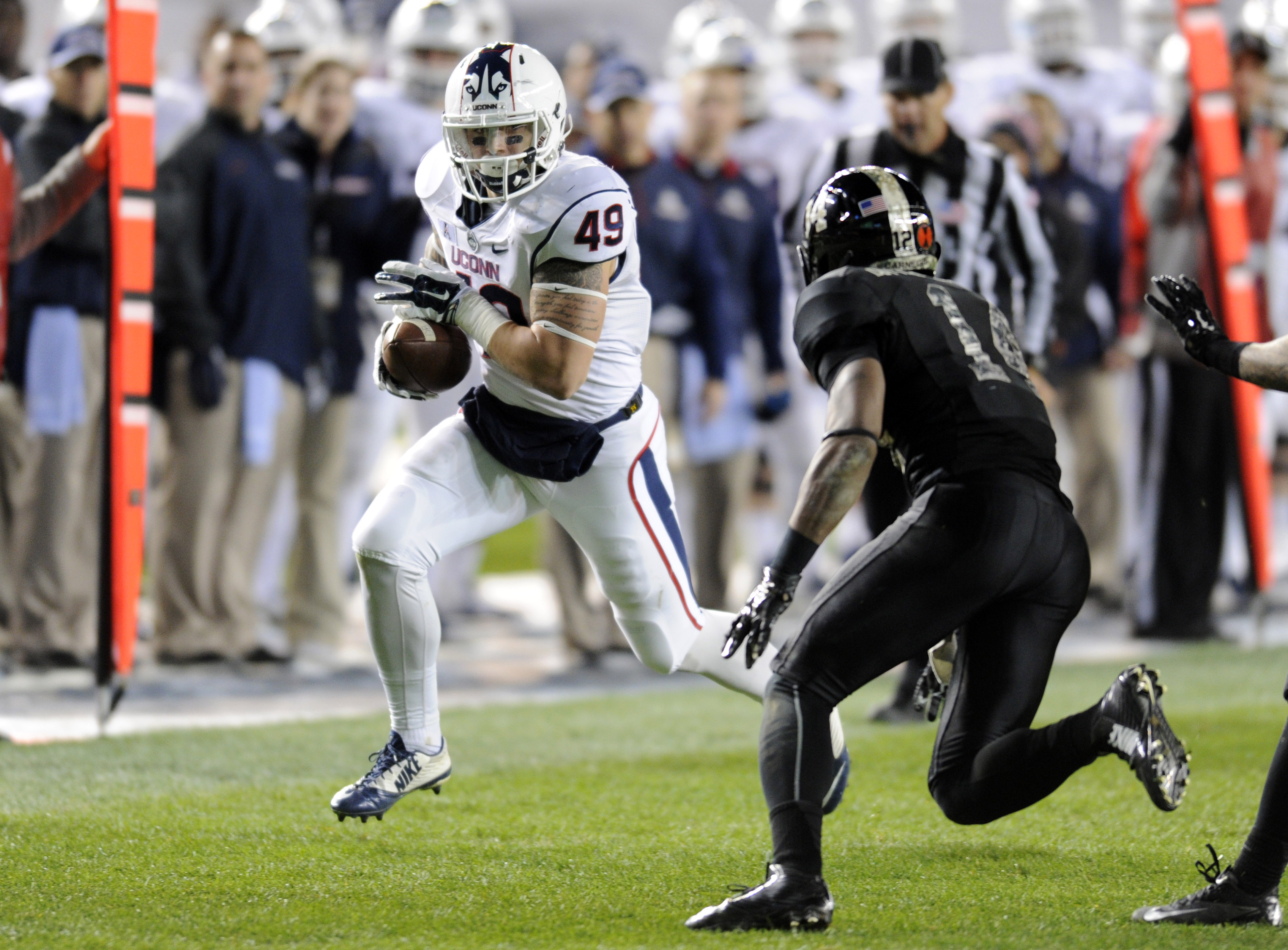 Connecticut tight end Sean McQuillan, left, runs with the ball as Army defensive back Chris Carnegie closes in during the second half of an NCAA college football game Saturday, Nov. 8, 2014, at Yankee Stadium in New York. Army won 35-21. (AP Photo/Bill Ko