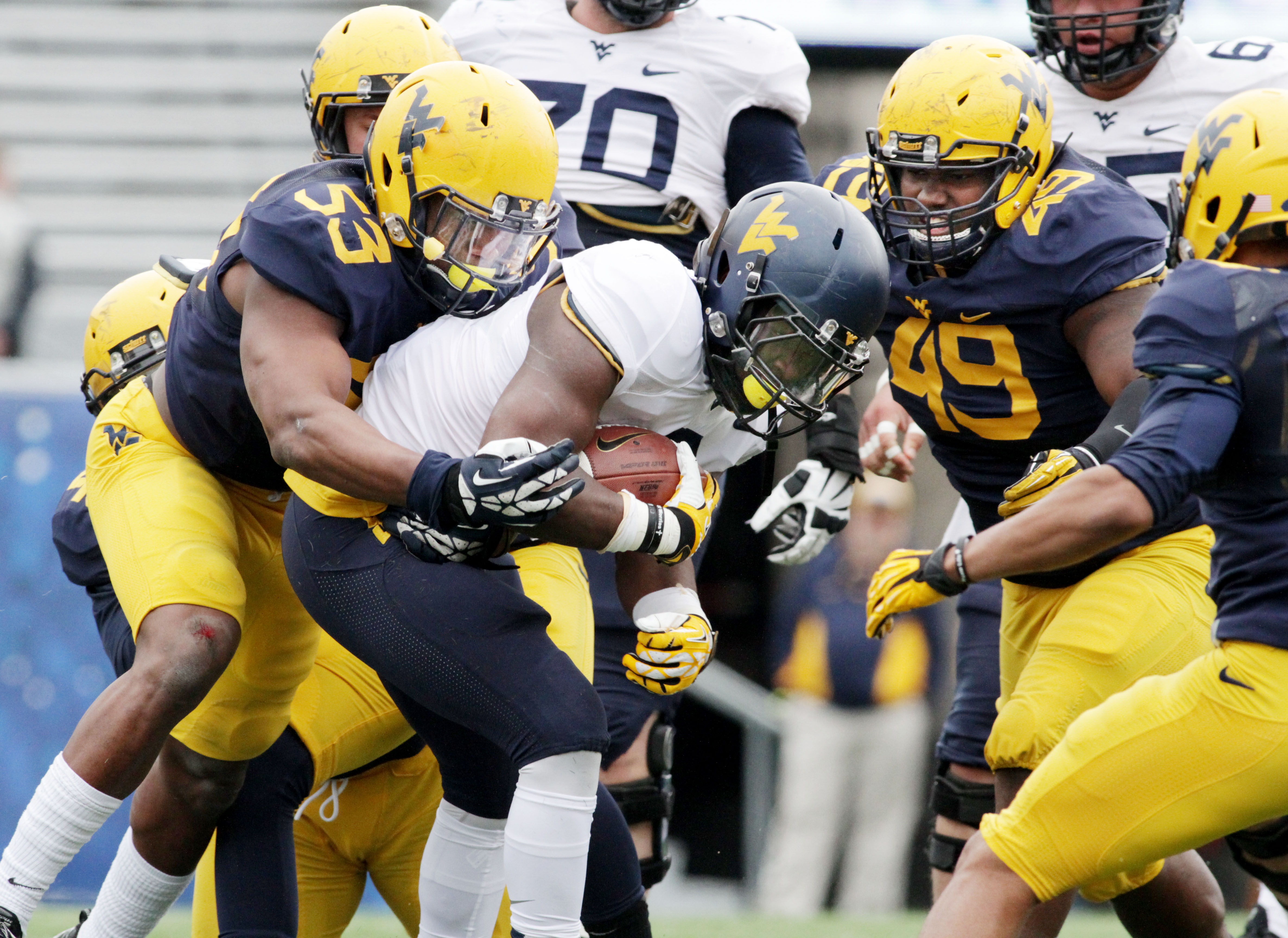 West Virginia linebacker Xavier Preston (53) tackles West Virginia running back Donte Thomas-Williams (8) during a spring NCAA college football scrimmage, Saturday, March, 25, 2015, in Morgantown, W.Va. (AP Photo/Raymond Thompson)