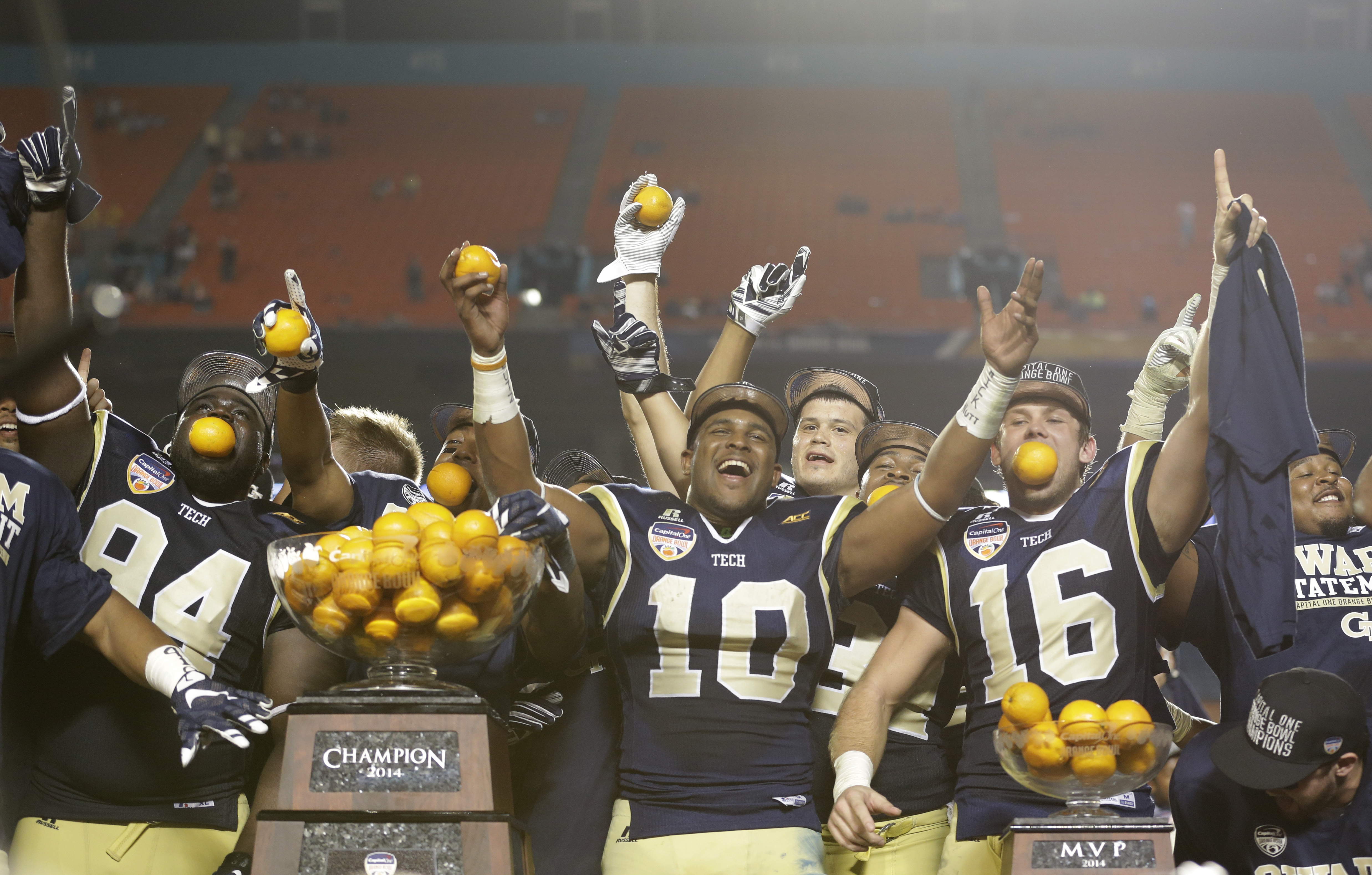 FILE - In this Dec. 31, 2014, file photo, Georgia Tech players celebrate with their trophy after Georgia Tech defeated Mississippi State 49-34 in the Orange Bowl NCAA college football game in Miami Gardens, Fla. Plenty has changed around the Atlantic Coas