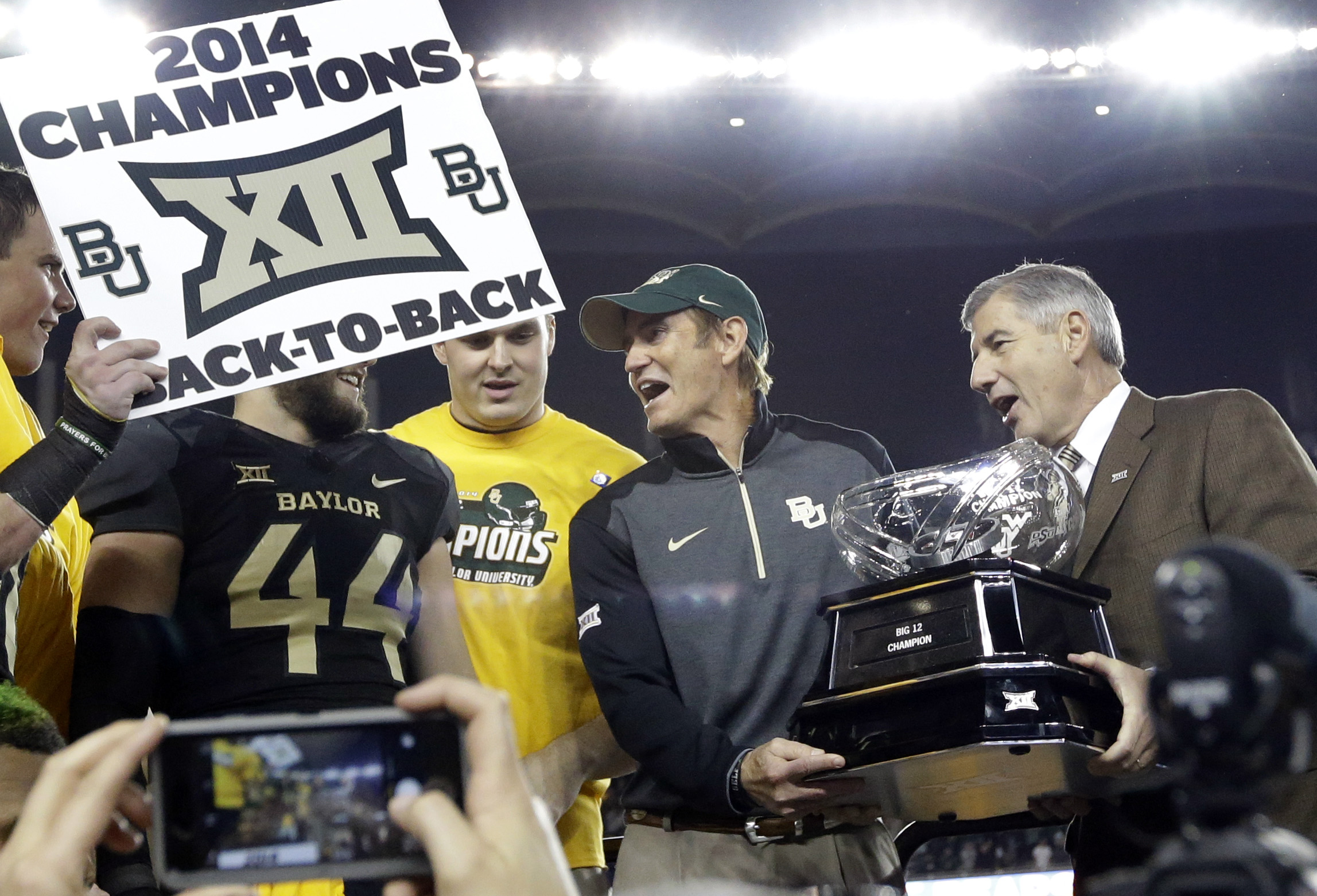 Big 12 Commissioner Bob Bowlsby, right, presents Baylor head coach Art Briles, center, with the conference trophy after their 38-27 win over Kansas State in an NCAA college football game, Saturday, Dec. 6, 2014, in Waco, Texas. (AP Photo/Tony Gutierrez)
