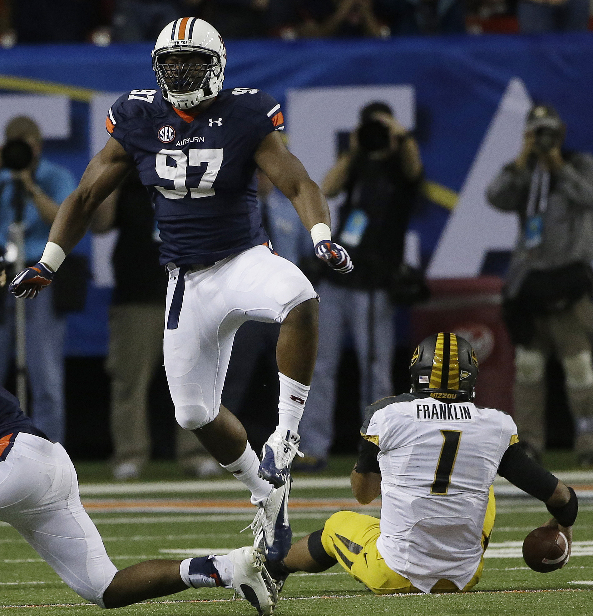 Auburn defensive end Elijah Daniel (97) celebrates sacking Missouri quarterback James Franklin (1) during the second half of the Southeastern Conference NCAA football championship game, Saturday, Dec. 7, 2013, in Atlanta. (AP Photo/John Bazemore)