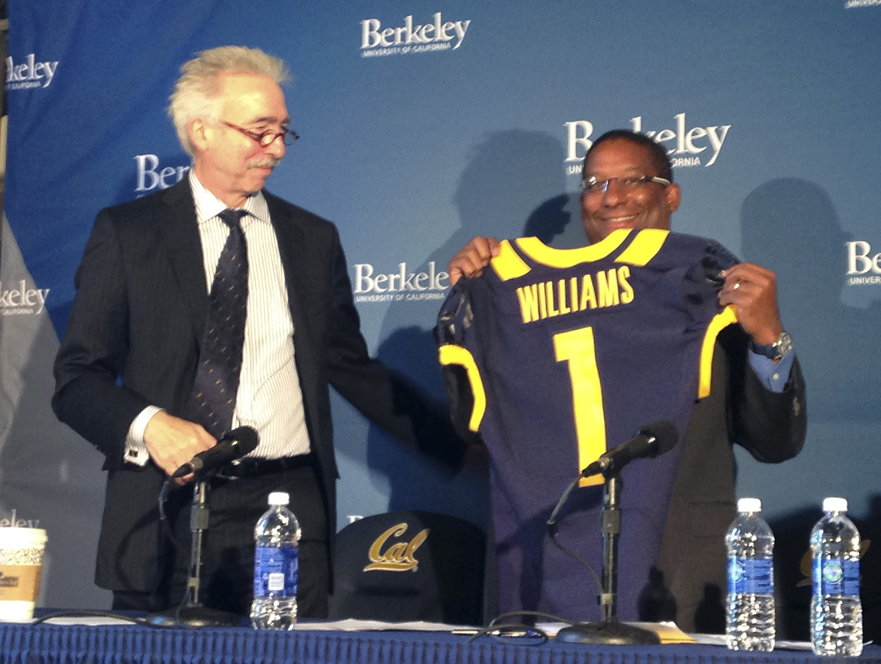 Chancellor Nicholas Dirks, left, presents a jersey to Michael Williams, right, after he was named the athletic director at the University of California, Berkeley Friday, May 8, 2015, in Berkeley, Calif. Williams insisted he didn't want to be California's