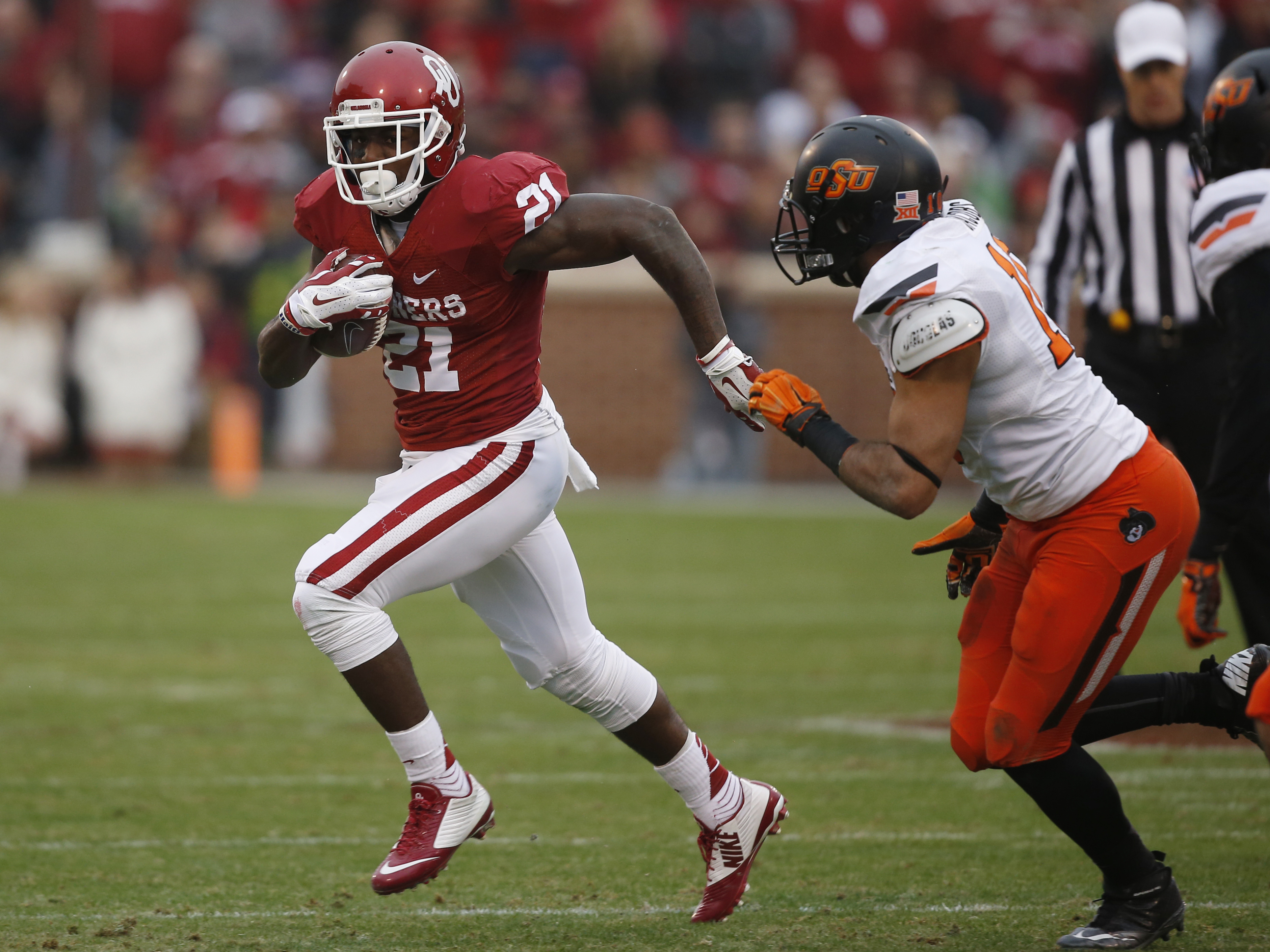 Oklahoma running back Keith Ford (21) carries past Oklahoma State cornerback Ramon Richards (18) during an NCAA college football game between Oklahoma State and Oklahoma in Norman, Okla., Saturday, Dec. 6, 2014. (AP Photo/Sue Ogrocki)