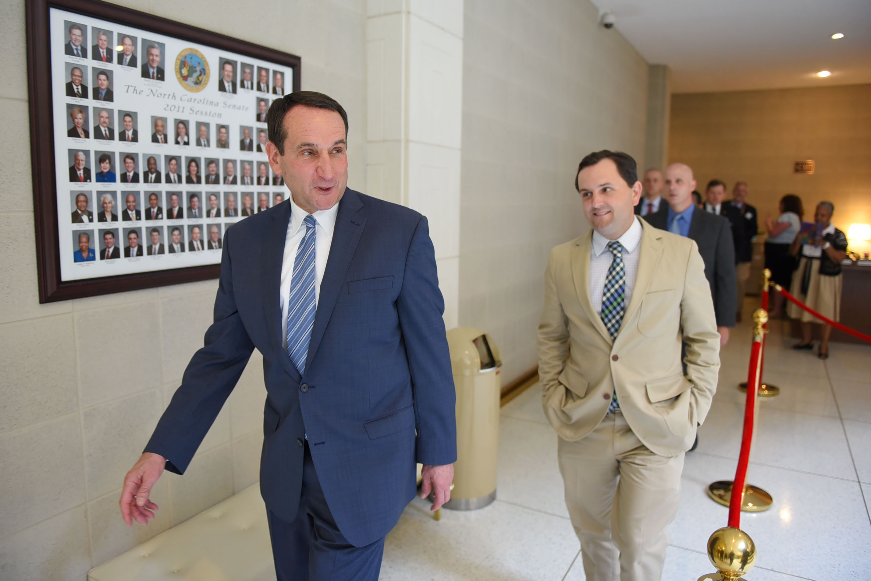 Duke men's basketball coach Mike Krzyzewski, left, walks to the Senate chamber with state Sen. Andrew C. Brock for a joint session of the North Carolina General Assembly on Tuesday, May 19, 2015 in Raleigh, N.C. The joint session passed SJR 714, honoring