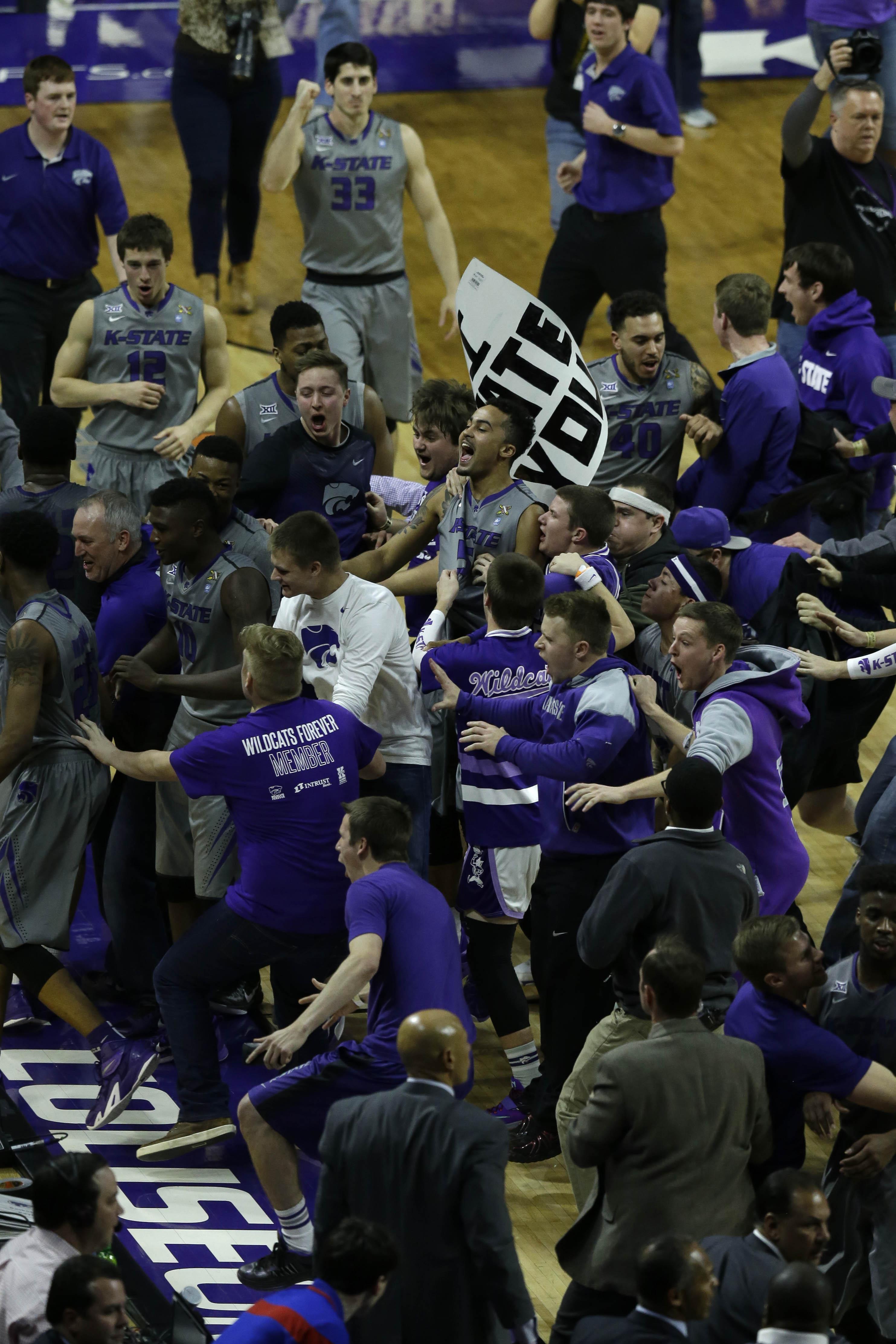 Kansas State players and fans celebrate following an NCAA college basketball game against Kansas at Bramlage Coliseum in Manhattan, Kan., Monday, Feb. 23, 2015. Kansas State defeated Kansas 70-63. (AP Photo/Orlin Wagner)