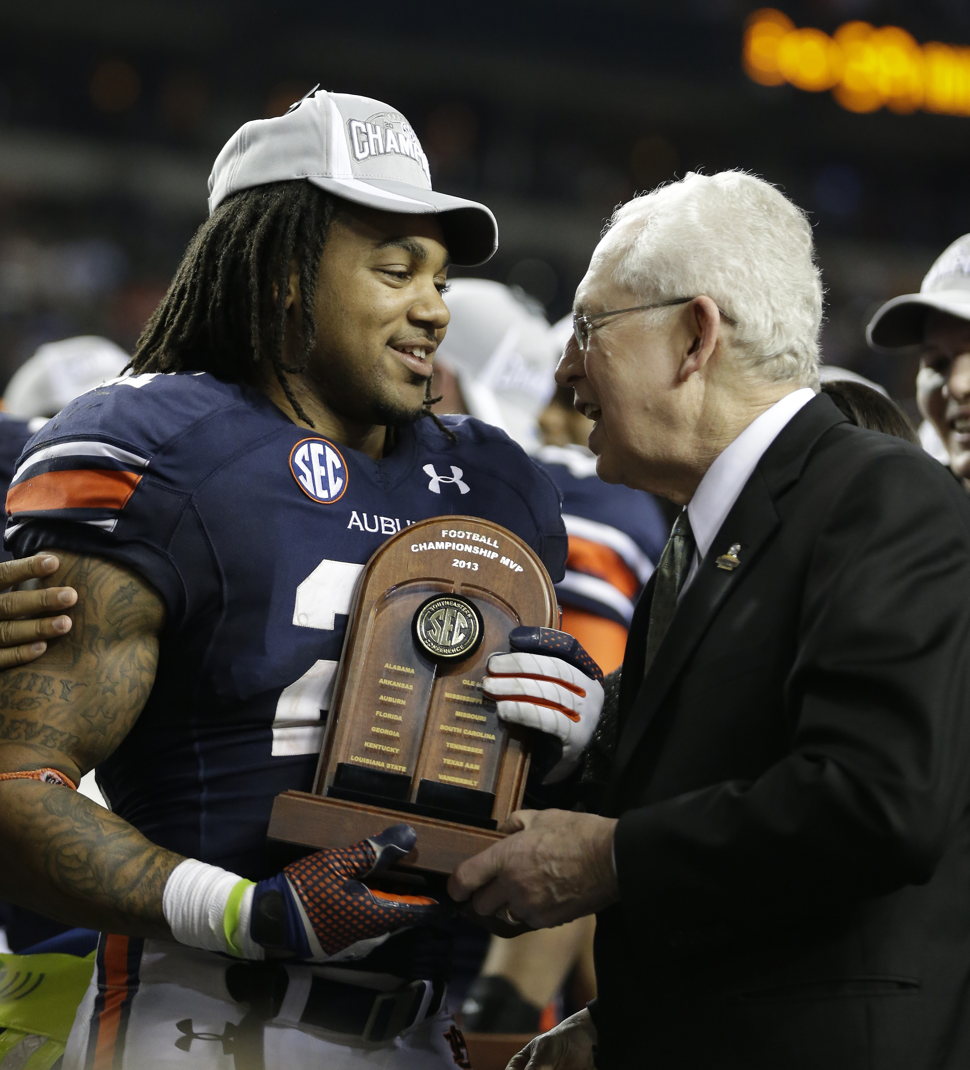 SEC Commissioner Mike Slive, right, presents the MVP trophy to Auburn running back Tre Mason after the second half of the Southeastern Conference NCAA football championship game against Missouri, Saturday, Dec. 7, 2013, in Atlanta. Auburn won 59-42. (AP P