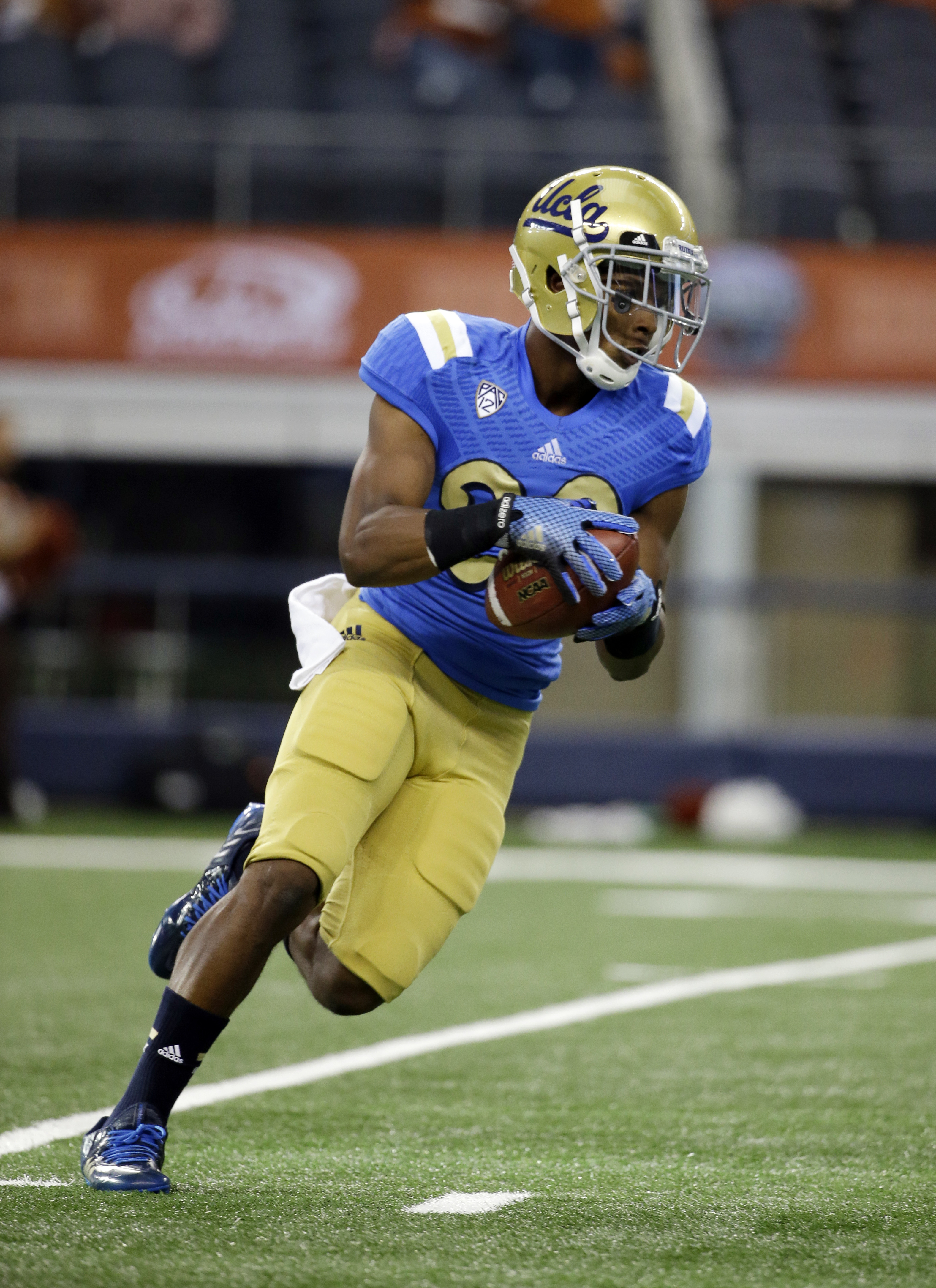 UCLA defensive back Justin Combs carries the ball after grabbing a pass during warm ups before an NCAA college football game against Texas, Saturday, Sept. 13, 2014, in Arlington, Texas. (AP Photo/Tony Gutierrez)