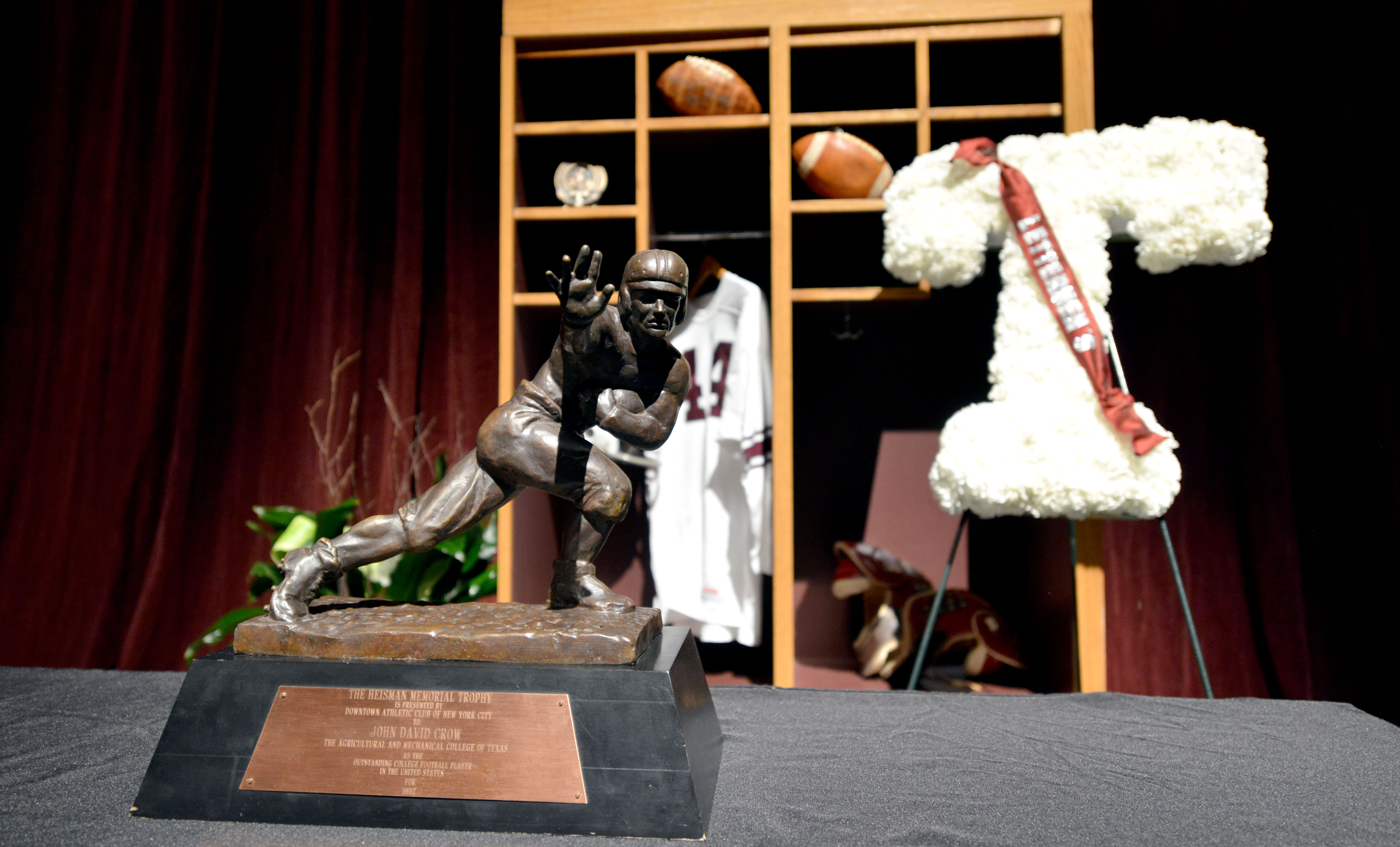 Texas A&M's John David Crow's Heisman trophy sits along side other memorabilia during a memorial service for Crow on Tuesday, June 23, 2015, at Reed Arena in College Station, Texas. Crow, the bruising running back who won the 1957 Heisman Trophy with Texa