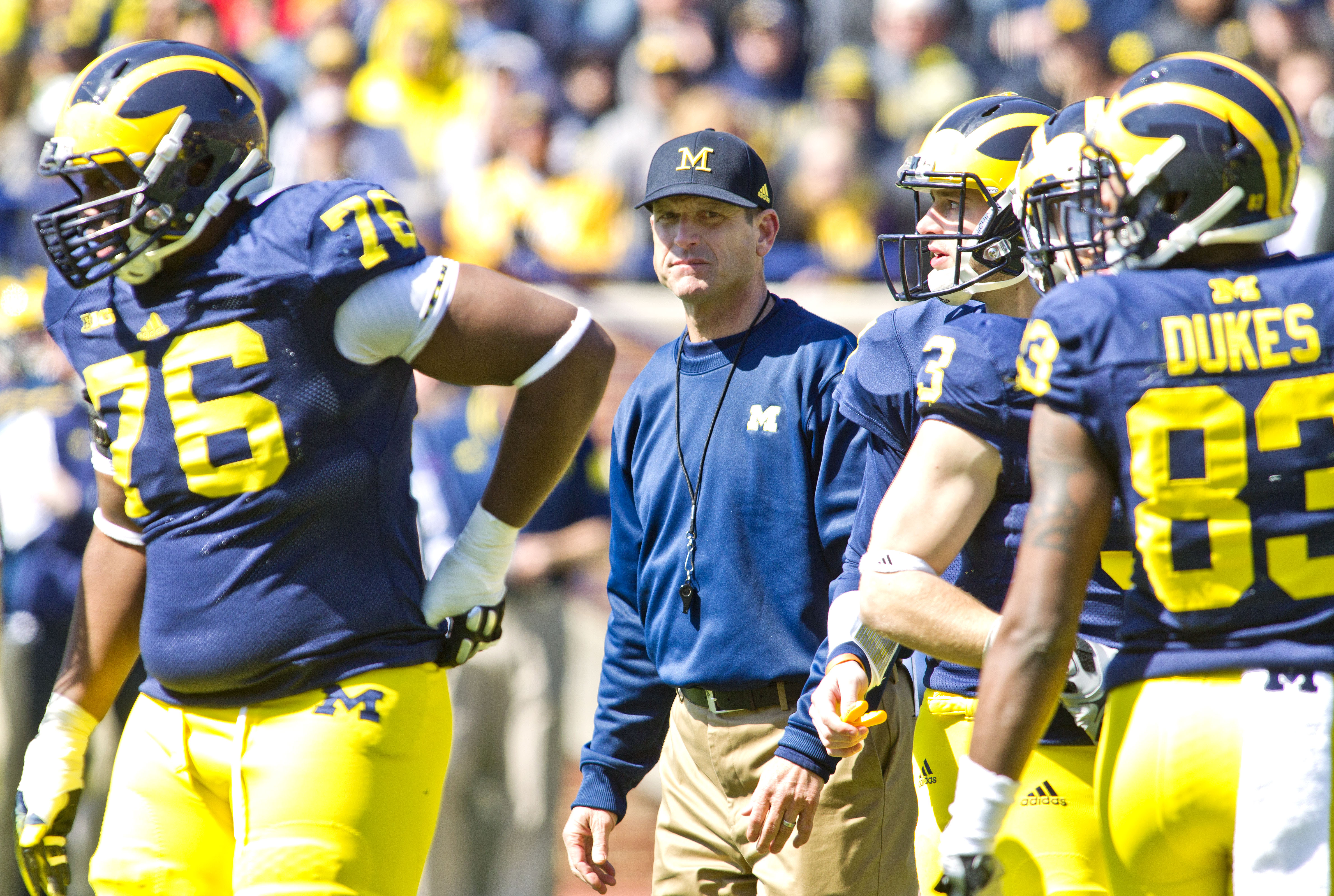 Michigan head coach Jim Harbaugh stands on the field amongst his players between downs during the NCAA college football team's spring game in Ann Arbor, Mich., Saturday, April 4, 2015. (AP Photo/Tony Ding)