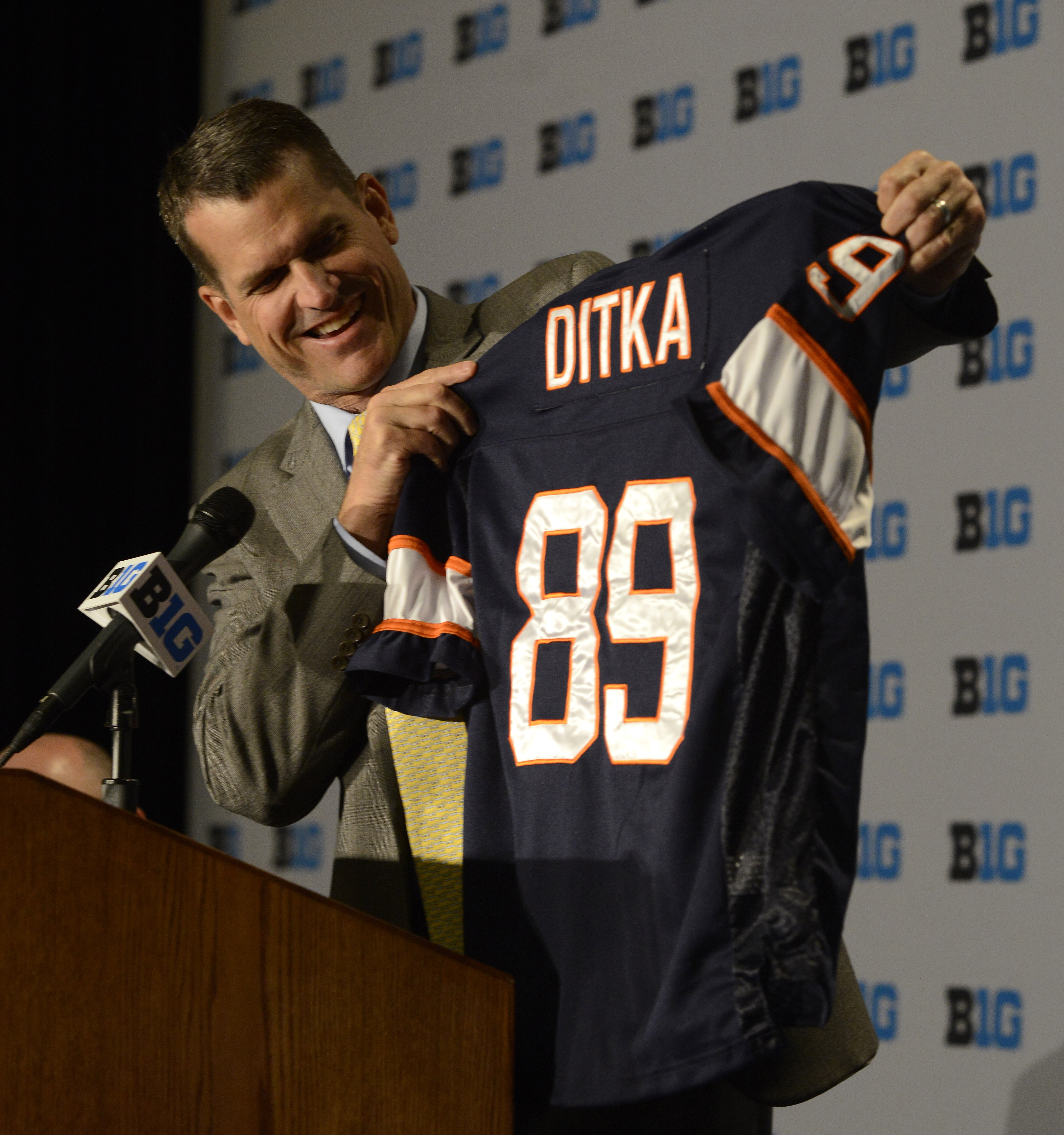 Michigan head coach Jim Harbaugh shows a jersey of his former Chicago Bears coach Mike Ditka while speaking to the media during the NCAA college Big Ten Football Media Day Friday, July 31, 2015 in Chicago. (AP Photo/Paul Beaty)