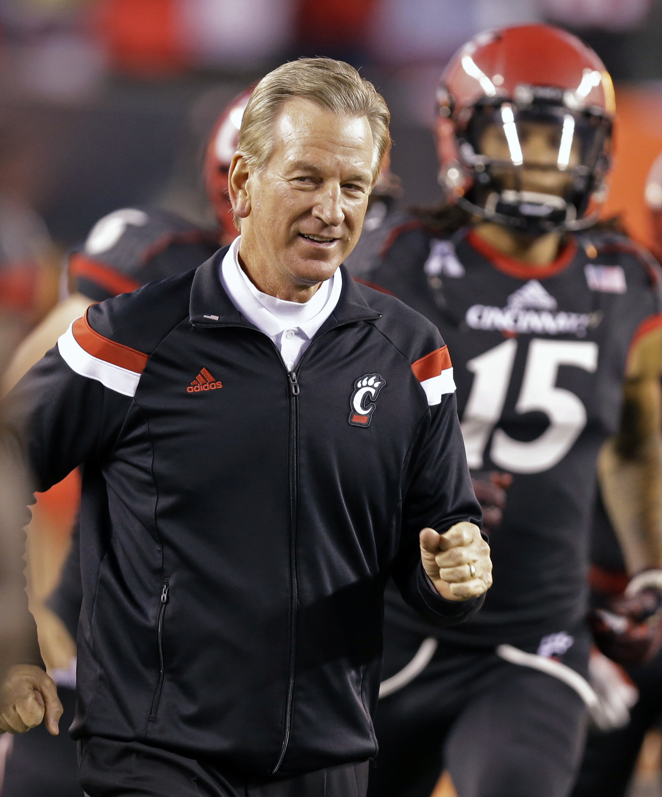 Cincinnati coach Tommy Tuberville runs onto the field at the start of an NCAA college football game against South Florida, Friday, Oct. 24, 2014, in Cincinnati. (AP Photo/Al Behrman)
