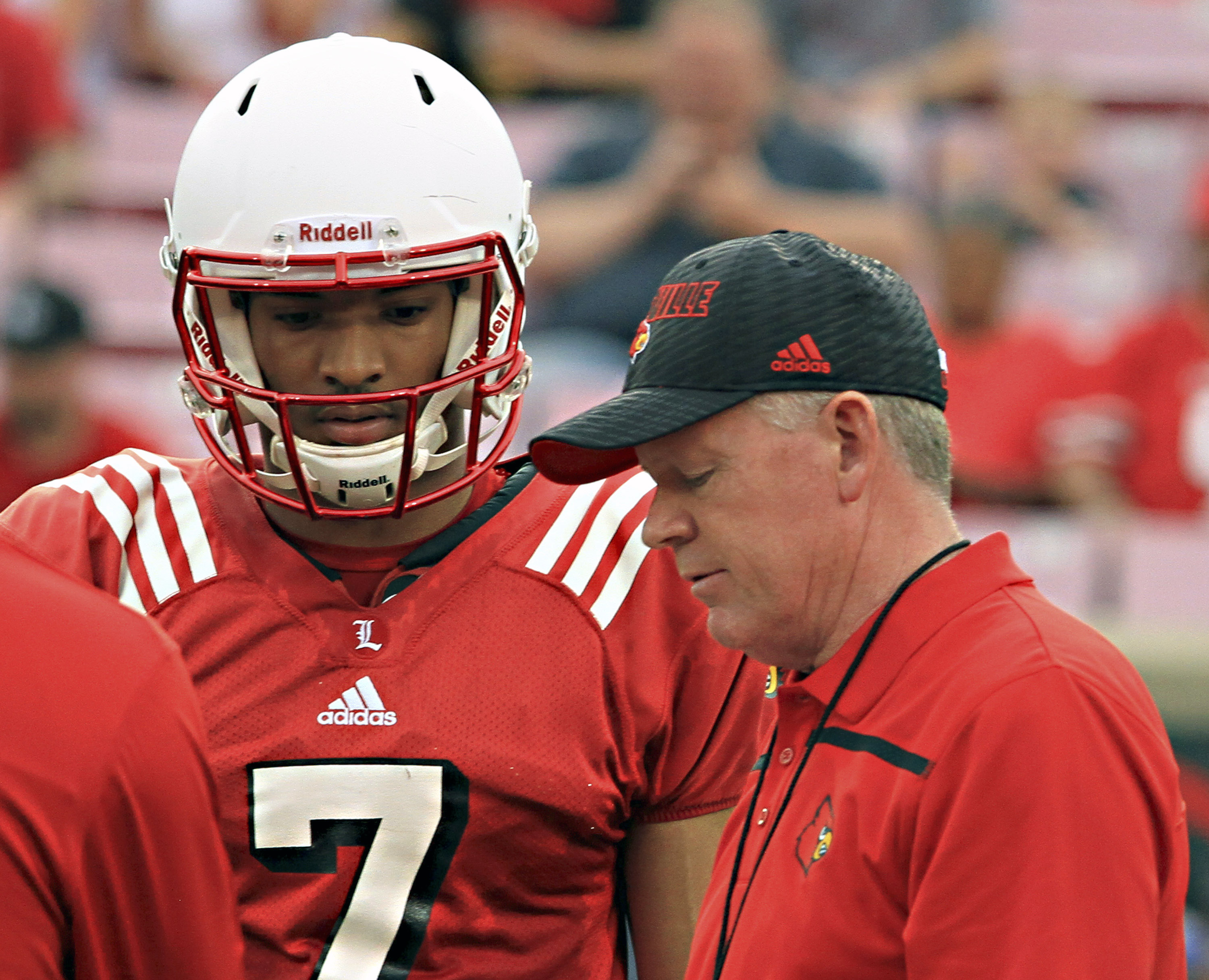 FILE - In this April 17, 2015, file photo, Louisville head football coach Bobby Petrino, right, talks over a play call with quarterback Reggie Bonnafon (7) during the annual spring football scrimmage game at Cardinal Stadium in Louisville, Ky. Having two