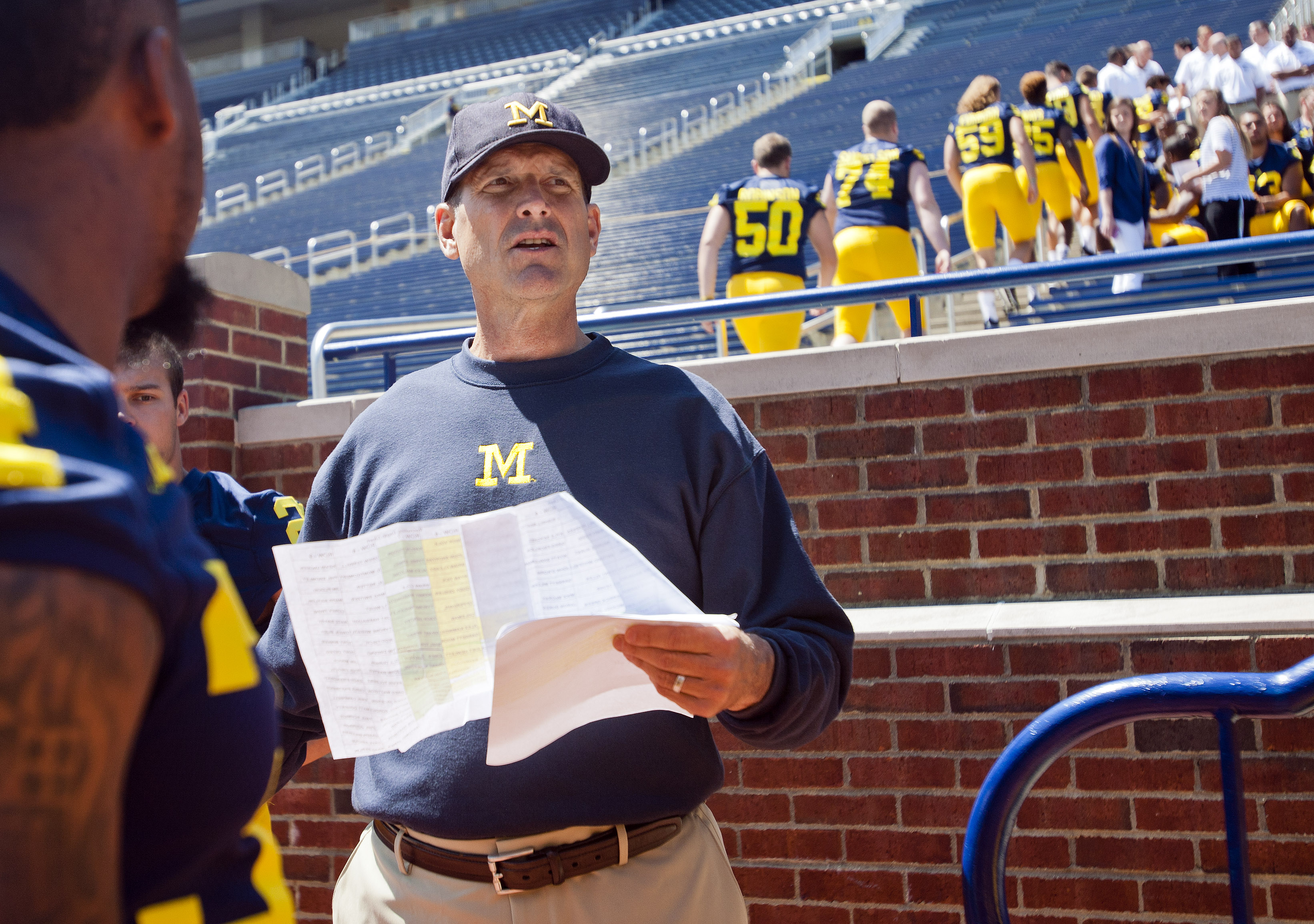 Michigan head coach Jim Harbaugh coordinates his players to lineup in the Michigan Stadium stands for a team photo, during the NCAA college football team's annual media day in Ann Arbor, Mich., Thursday, Aug. 6, 2015. (AP Photo/Tony Ding)