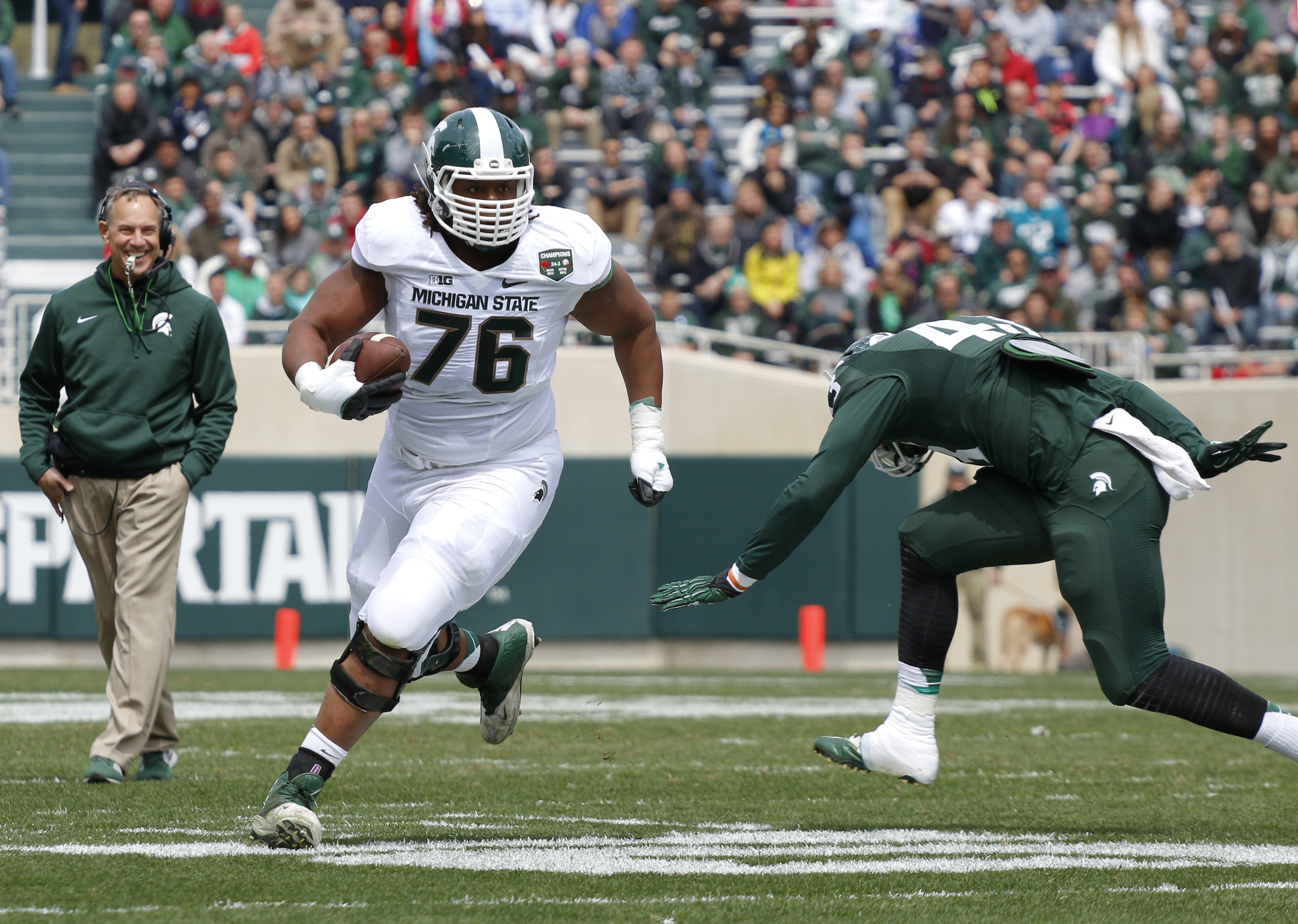 Michigan State White Team offensive lineman Donavan Clark (76) runs on a pass reception against the Green Team's Ed Davis, right, as head coach Mark Dantonio, left, watches during the Spartans' spring NCAA college football game, Saturday, April 25, 2015,