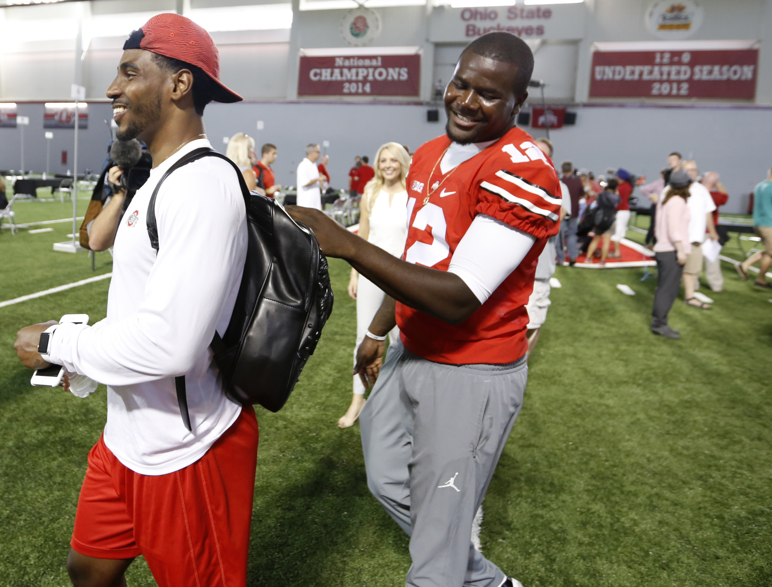 Ohio State quarterback Cardale Jones, right, jokes with former quarterback turned wide receiver Braxton Miller during the university's NCAA college football media day in Columbus, Ohio, Sunday, Aug. 16, 2015. (AP Photo/Paul Vernon)