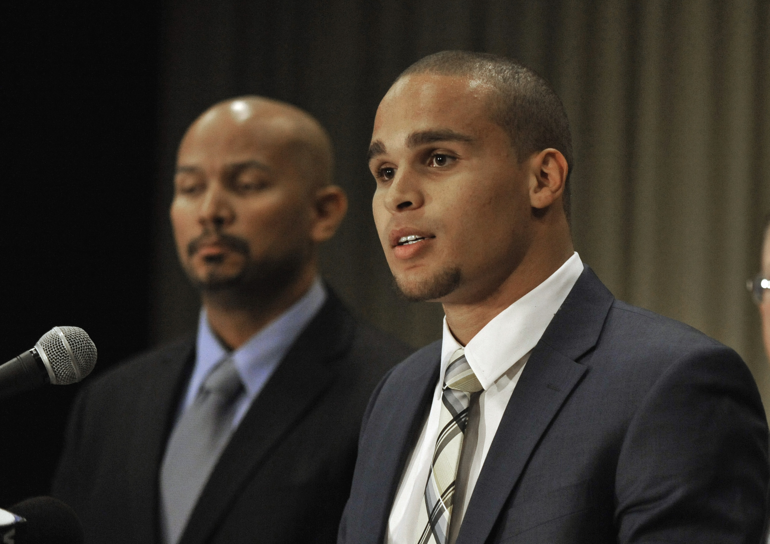 FILE - In this Jan. 28, 2014 file photo, Northwestern quarterback Kain Colter, right, speaks while College Athletes Players Association President Ramogi Huma, listens during a news conference in Chicago. The National Labor Relations Board has dismissed a