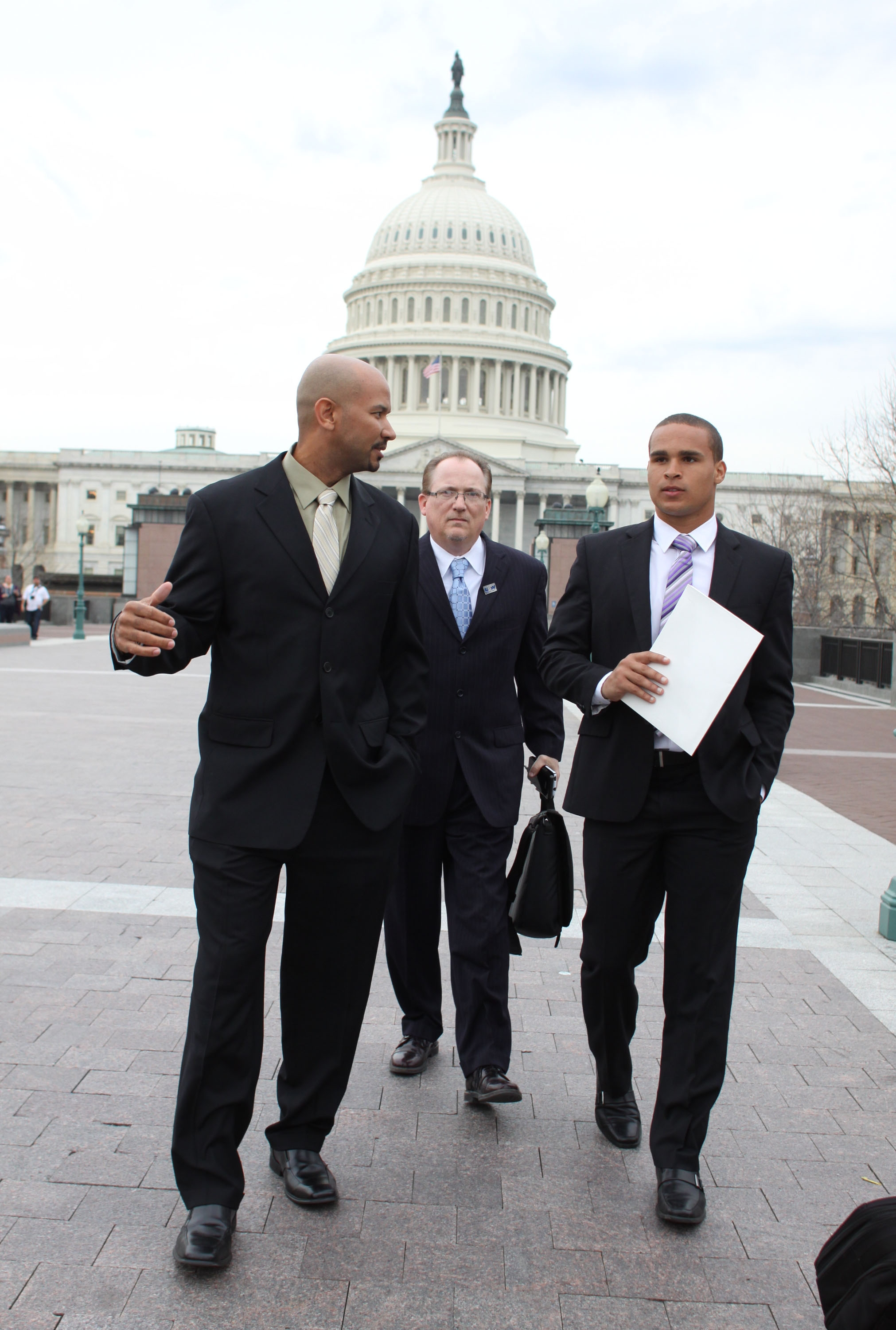 FILE - In this April 2, 2014, file photo, former Northwestern University football quarterback Kain Colter, right, Ramogi Huma, founder and President of the National College Players Association left, and Tim Waters, Political Director of the United Steel W