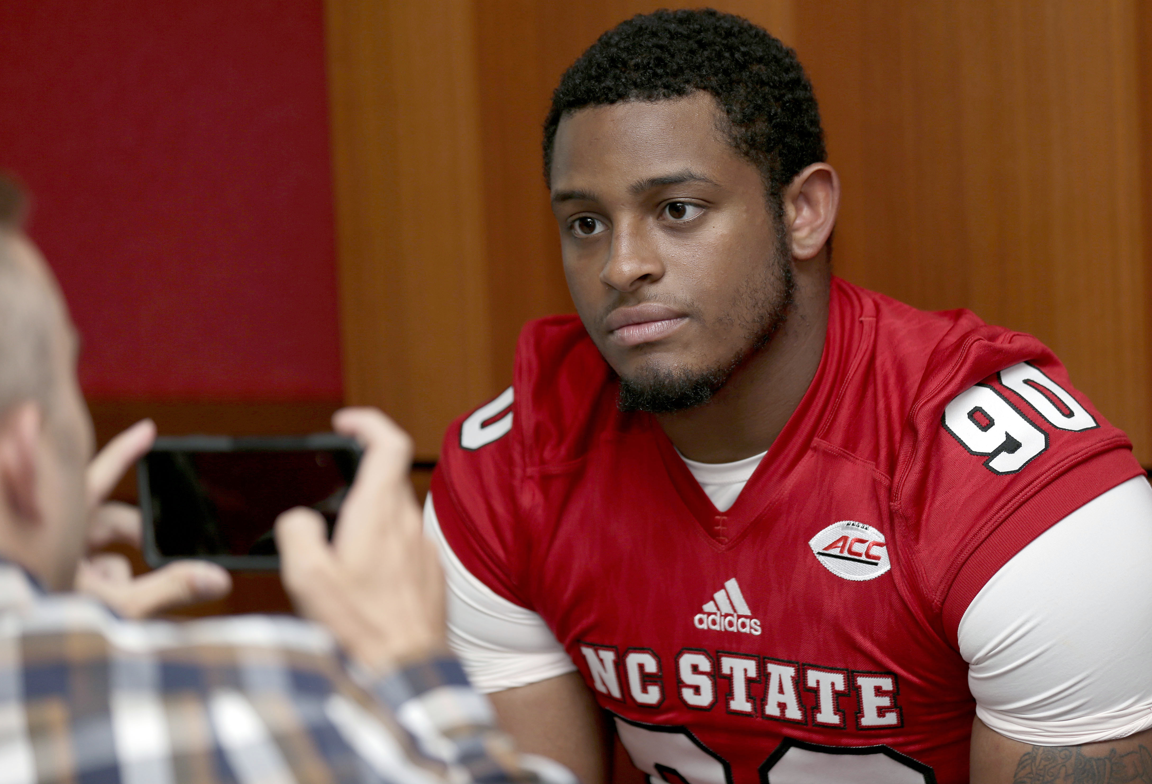 In this photo taken Sunday, Aug. 9, 2015, North Carolina State defensive end Mike Rose (90) speaks with members of the press during the team's NCAA college football media day in Raleigh, N.C. (AP Photo/Gerry Broome)