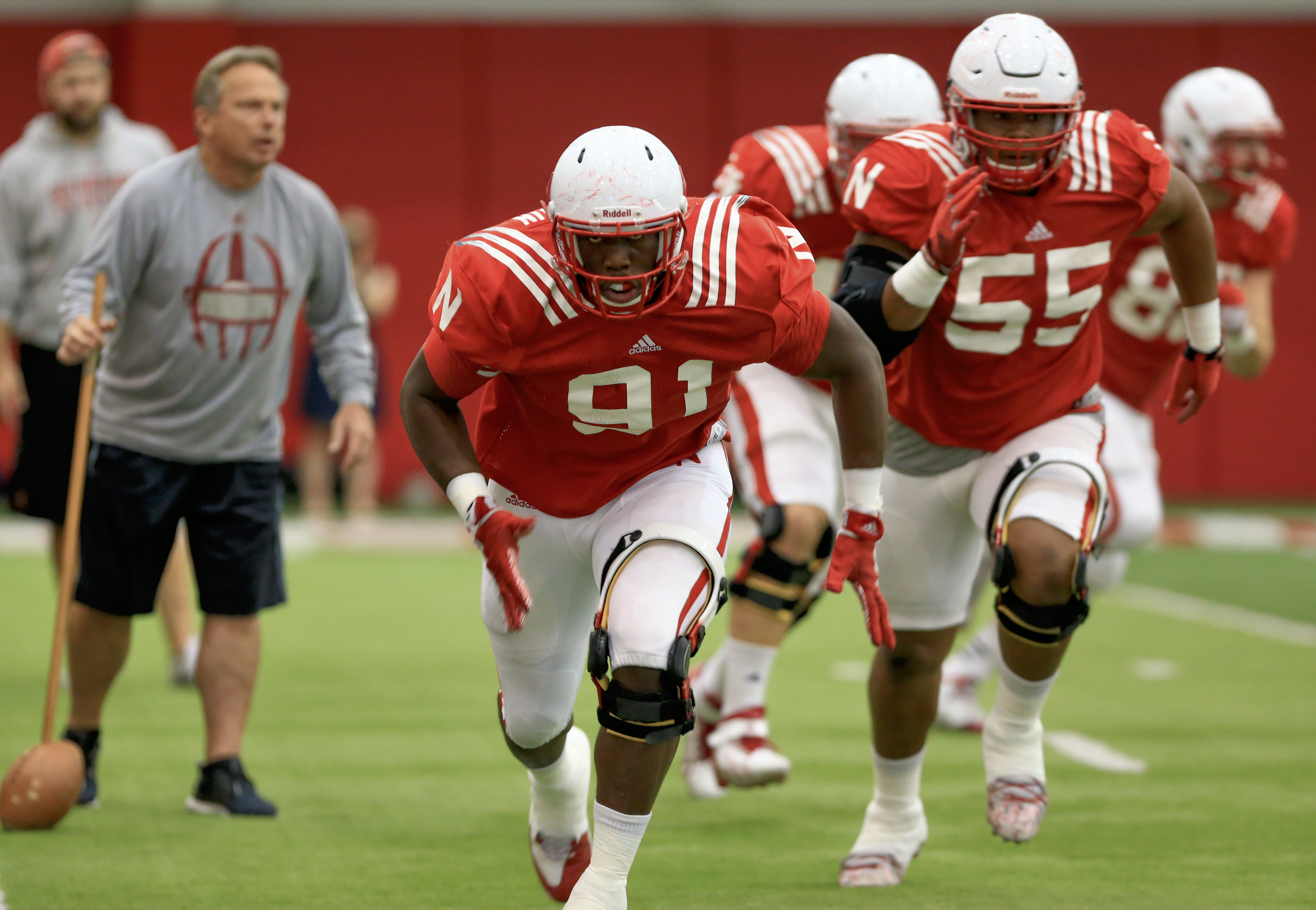 In this photo taken Aug. 18, 2015, Nebraska defensive end Freedom Akinmoladun (91) and defensive tackle Kevin Maurice (55) are followed by defensive coordinator Mark Banker, left,  during NCAA college football practice in Lincoln, Neb. Nebraska returns si