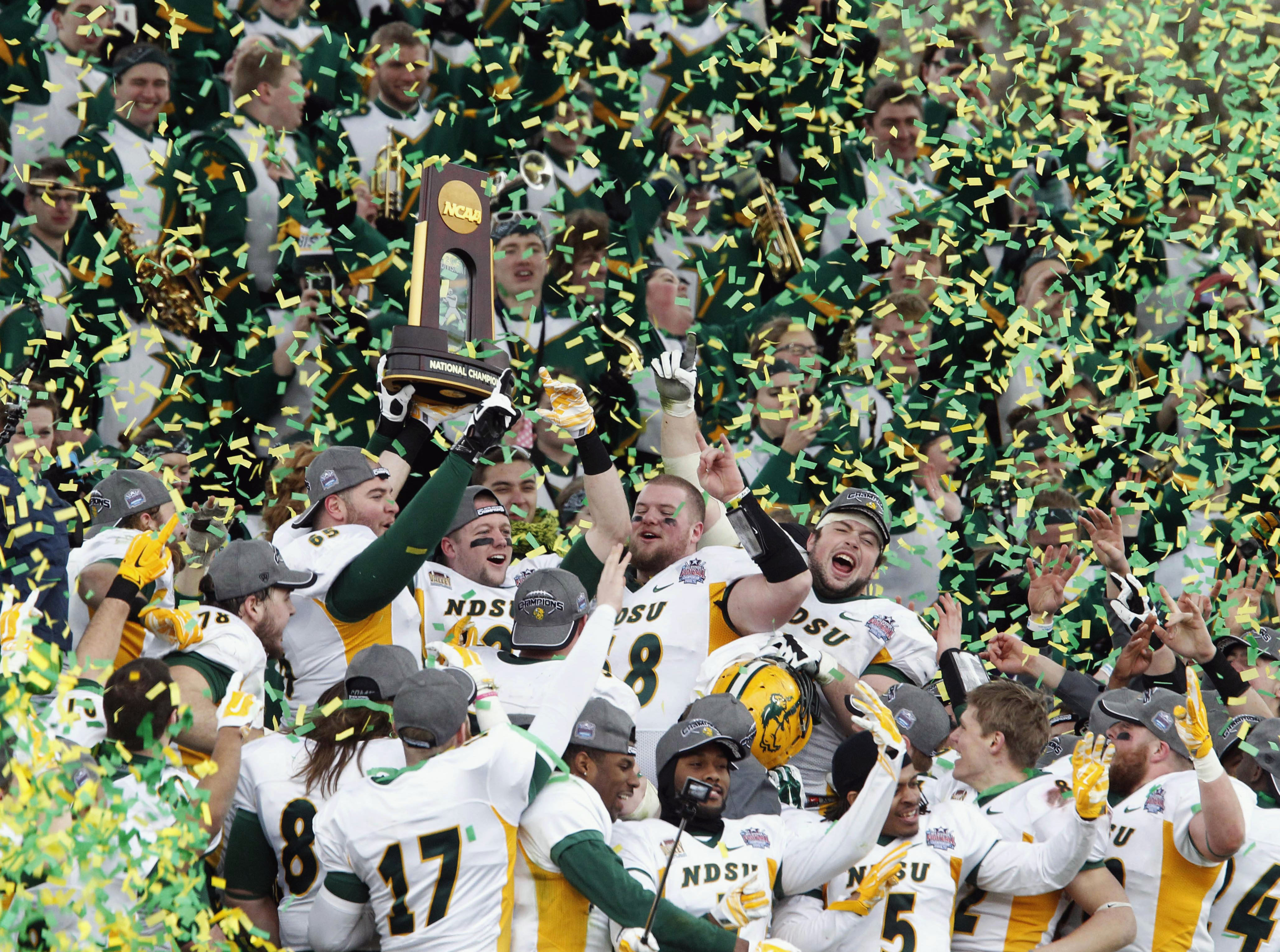 FILE - In this Jan. 10, 2015 file photo, members of the North Dakota State football team hold the championship trophy after their 29-27 win over Illinois State in the FCS Championship NCAA college football game in Frisco, Texas.  NDSU says it will start p