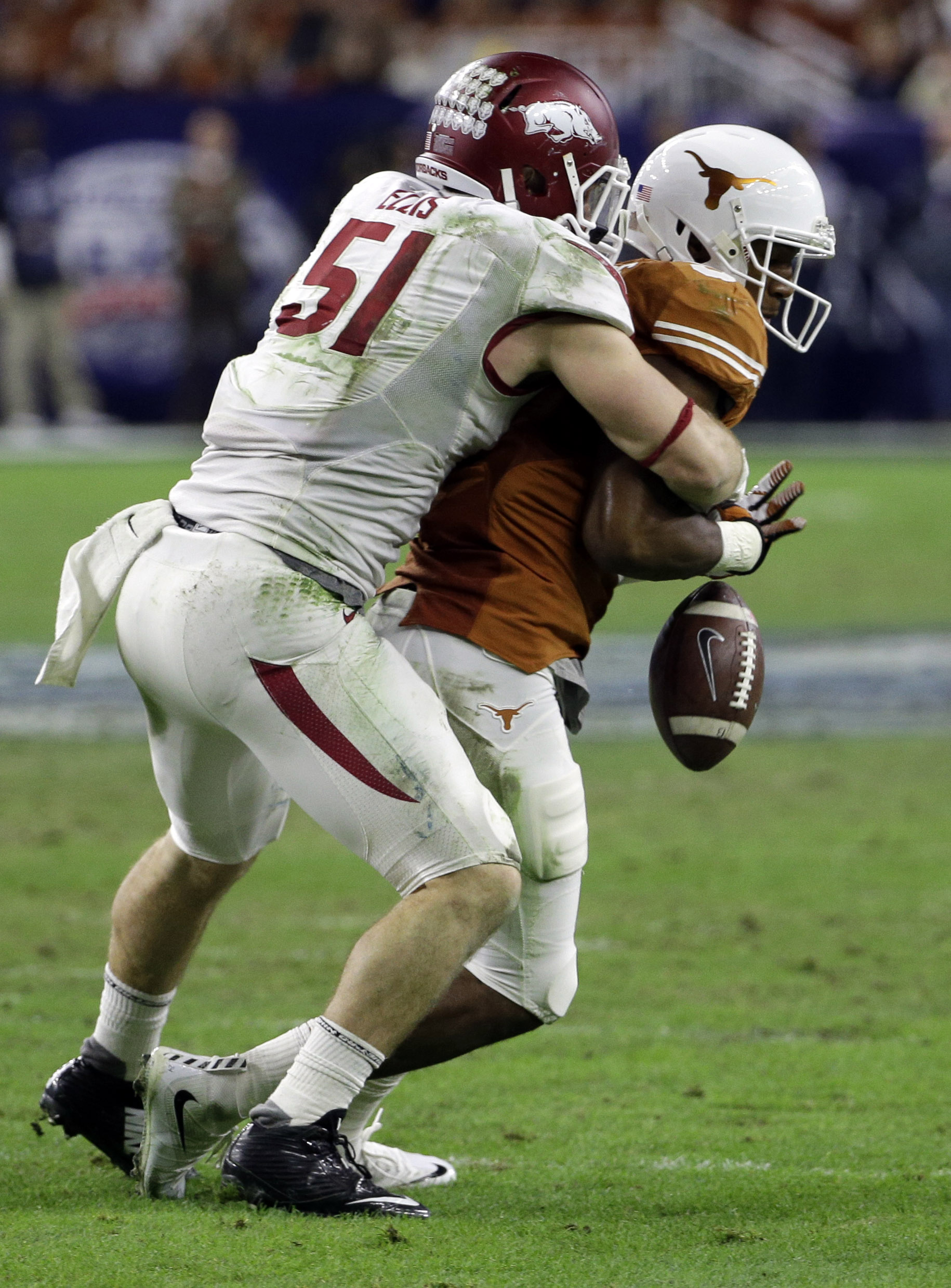 FILE - In this file photo taken  Dec. 29, 2014, Texas wide receiver John Harris (9) fumbles the ball as he is hit by Arkansas linebacker Brooks Ellis (51) during the second half of the Texas Bowl NCAA college football game in Houston. Arkansas ended last