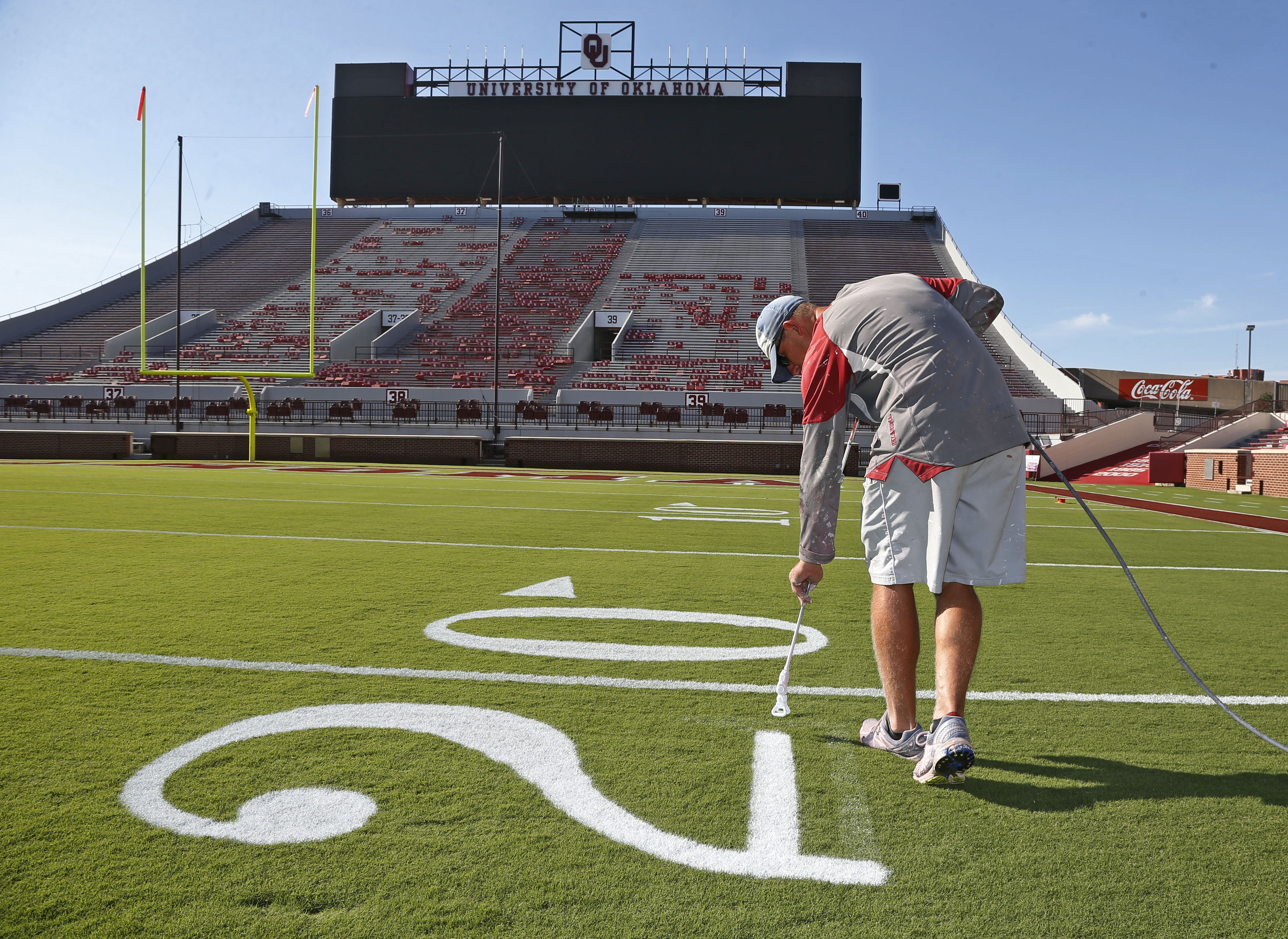 Grounds crew member Cliff Brunken paints yard line numbers on Owen Field in Norman, Okla., Thursday, Sept. 3, 2015, in preparation for Oklahoma's first game of the season. Oklahoma faces Akron on Saturday, Sept. 5, 015. (AP Photo/Sue Ogrocki)