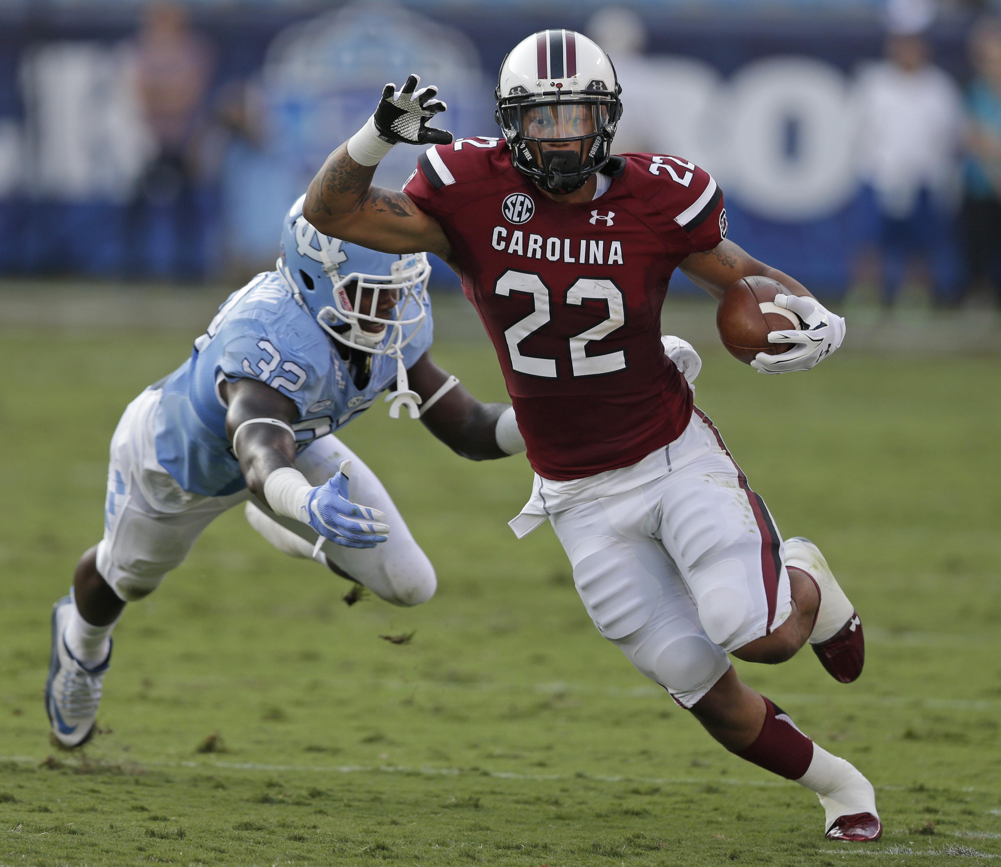 South Carolina's Brandon Wilds (22) runs past North Carolina's Joe Jackson (32) in the first half of an NCAA college football game in Charlotte, N.C., Thursday, Sept. 3, 2015. (AP Photo/Chuck Burton)