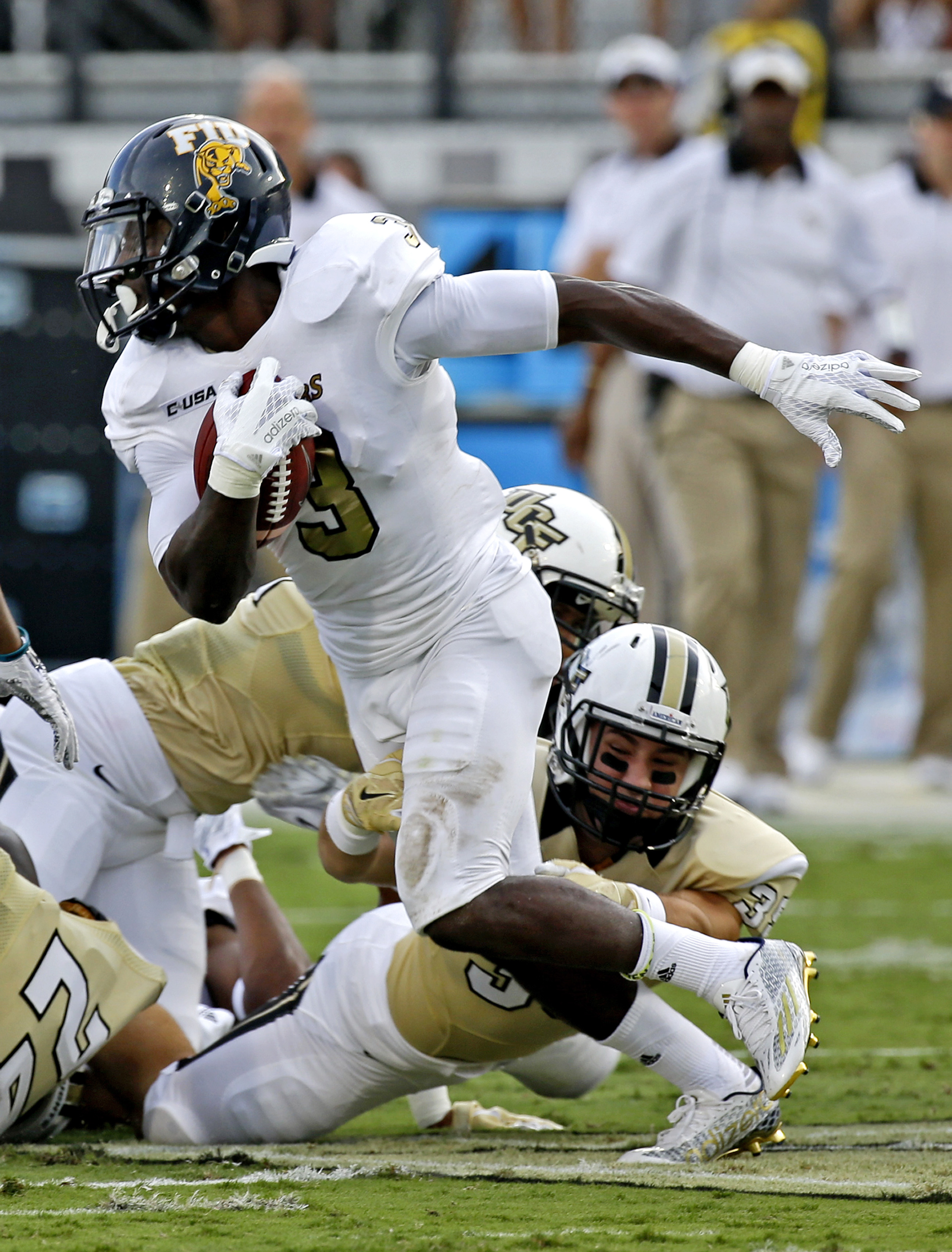 Florida International's Richard Leonard, left, is stopped by Central Florida's Brendin Straubel, lower right, on a kick return during the first half of an NCAA college football game, Thursday, Sept. 3, 2015, in Orlando, Fla. (AP Photo/John Raoux)