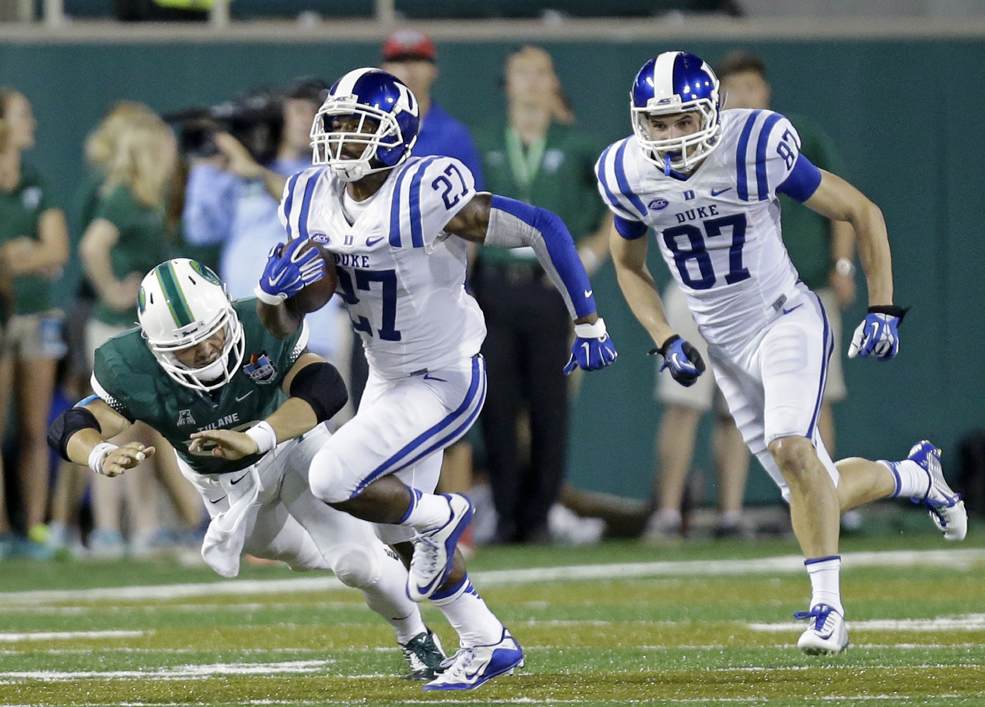 Duke safety DeVon Edwards (27) carries past Tulane's Marshall Wadleigh on a 95-yard kickoff return for a touchdown in the second half of an NCAA college football game in New Orleans, Thursday, Sept. 3, 2015. At right is Duke's Max McCaffrey (87). (AP Phot