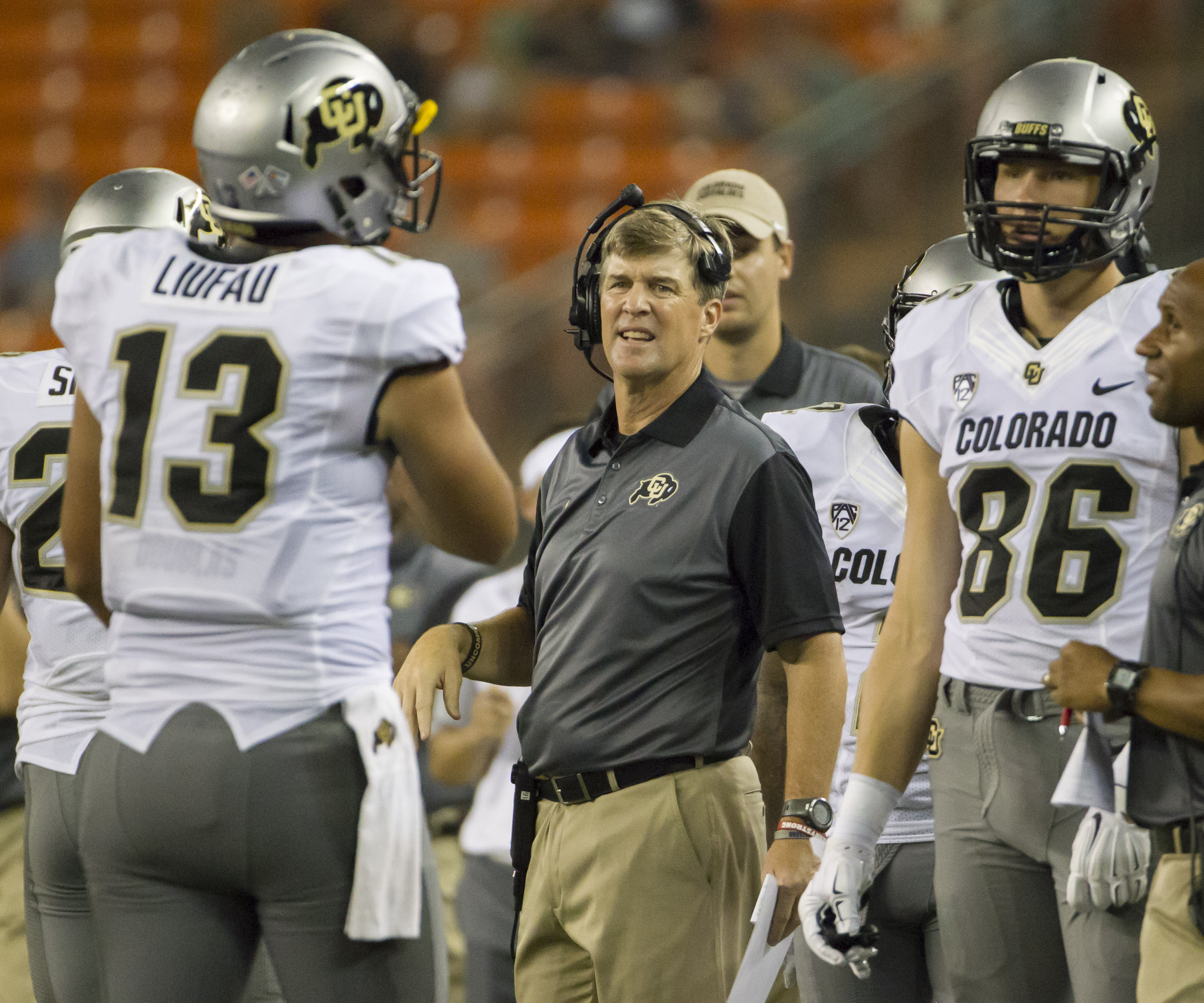 Colorado head coach Mike MacIntyre, center, gets ready to talk to his team during a timeout as Colorado quarterback Sefo Liufau (13) and tight end Dylan Keeney (86) look on in the second quarter of an NCAA college football game, Thursday, Sept. 3, 2015, i