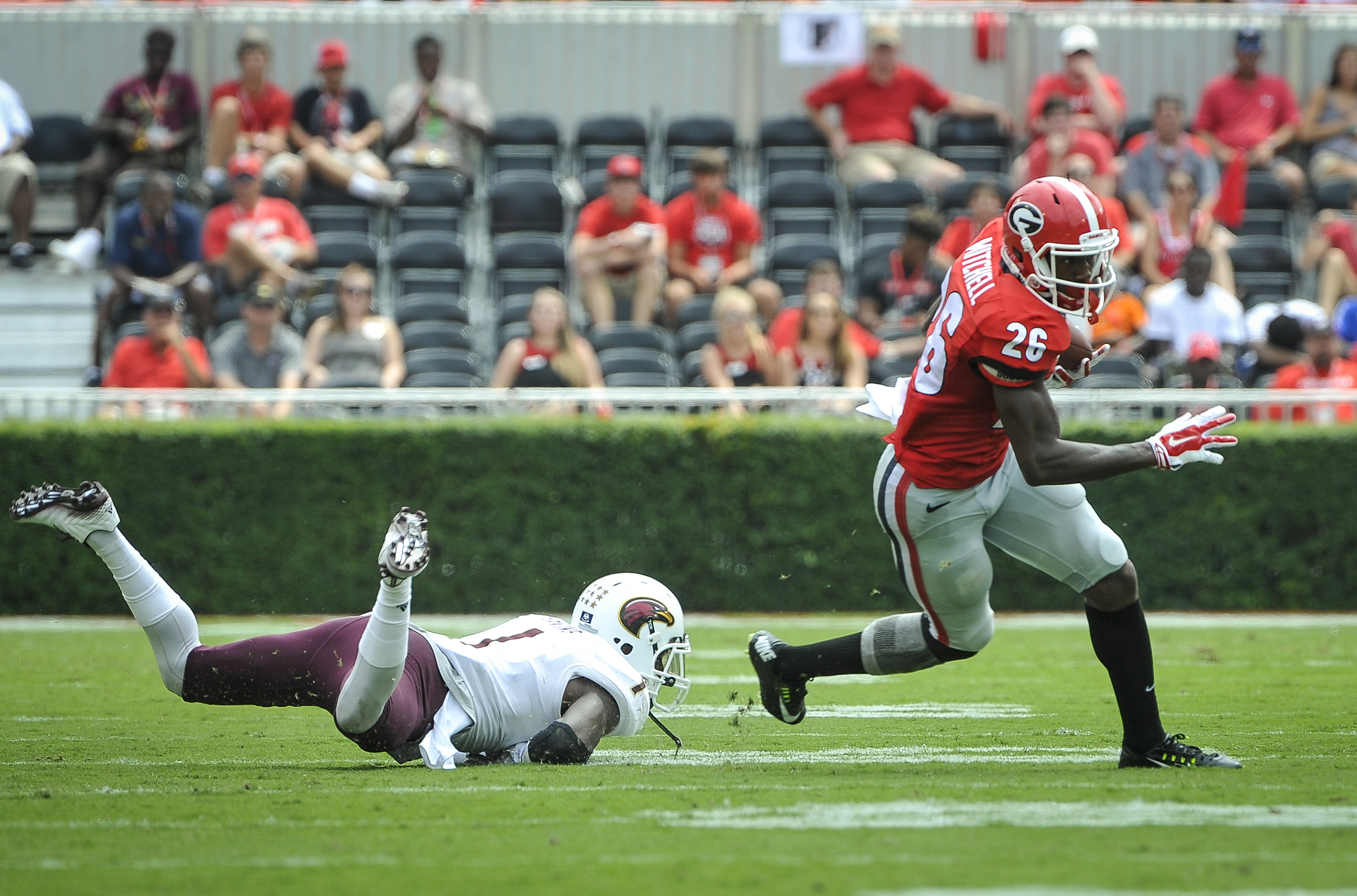 Georgia wide receiver Malcolm Mitchell (26) avoids the tackle by Louisiana Monroe cornerback Lenzy Pipkins (1) during the first half of an NCAA college football game, Saturday, Sept., 5, 2015, in Athens, Ga. (AP Photo/John Amis)