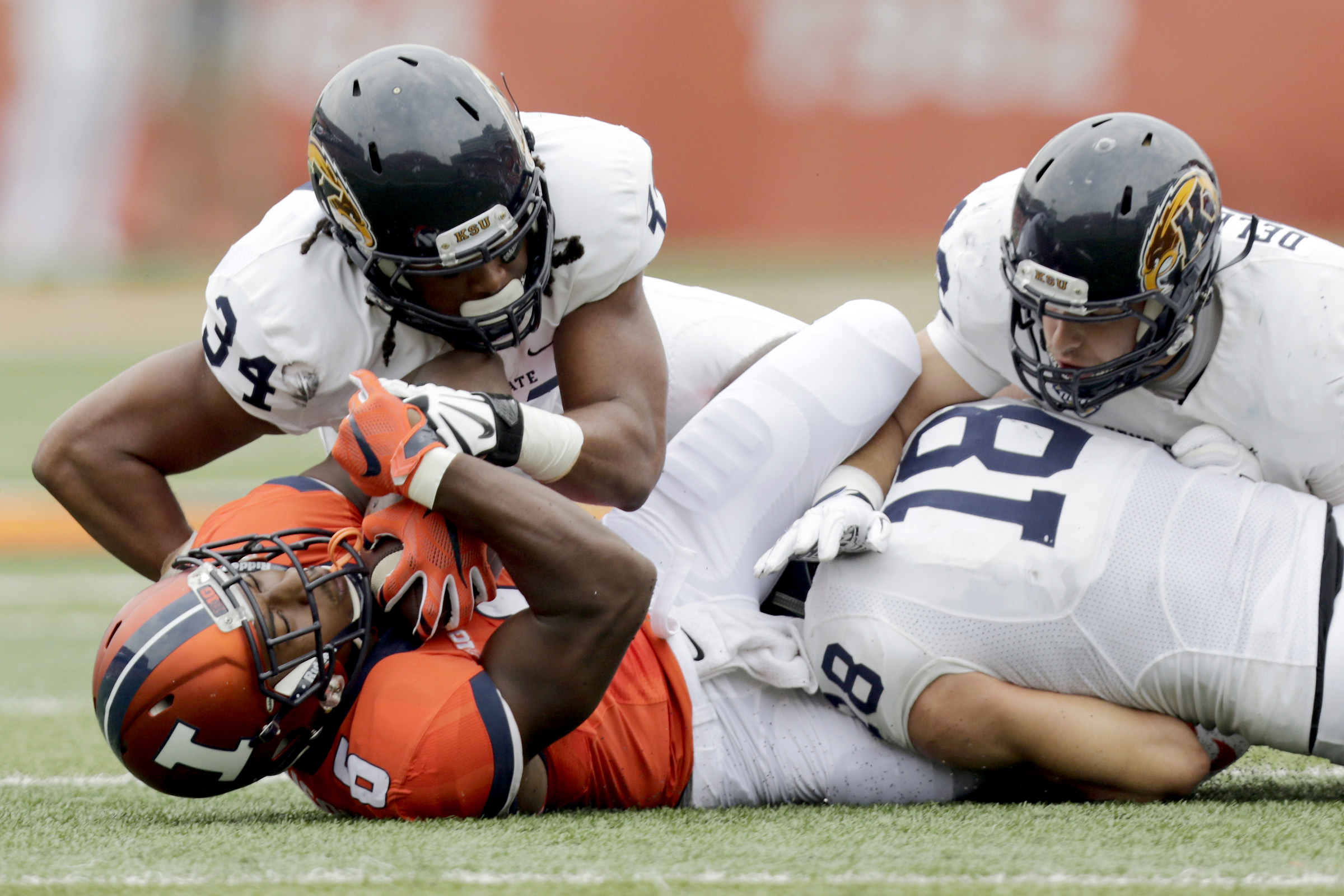 Kent State defensive end Anthony Johnson (34), linebacker Matt Dellinger (32) and safety Nate Holley (18) wrap up Illinois running back Josh Ferguson (6) during the first half of an NCAA college football game Saturday, Sept. 5, 2015, in Champaign, Ill. (A