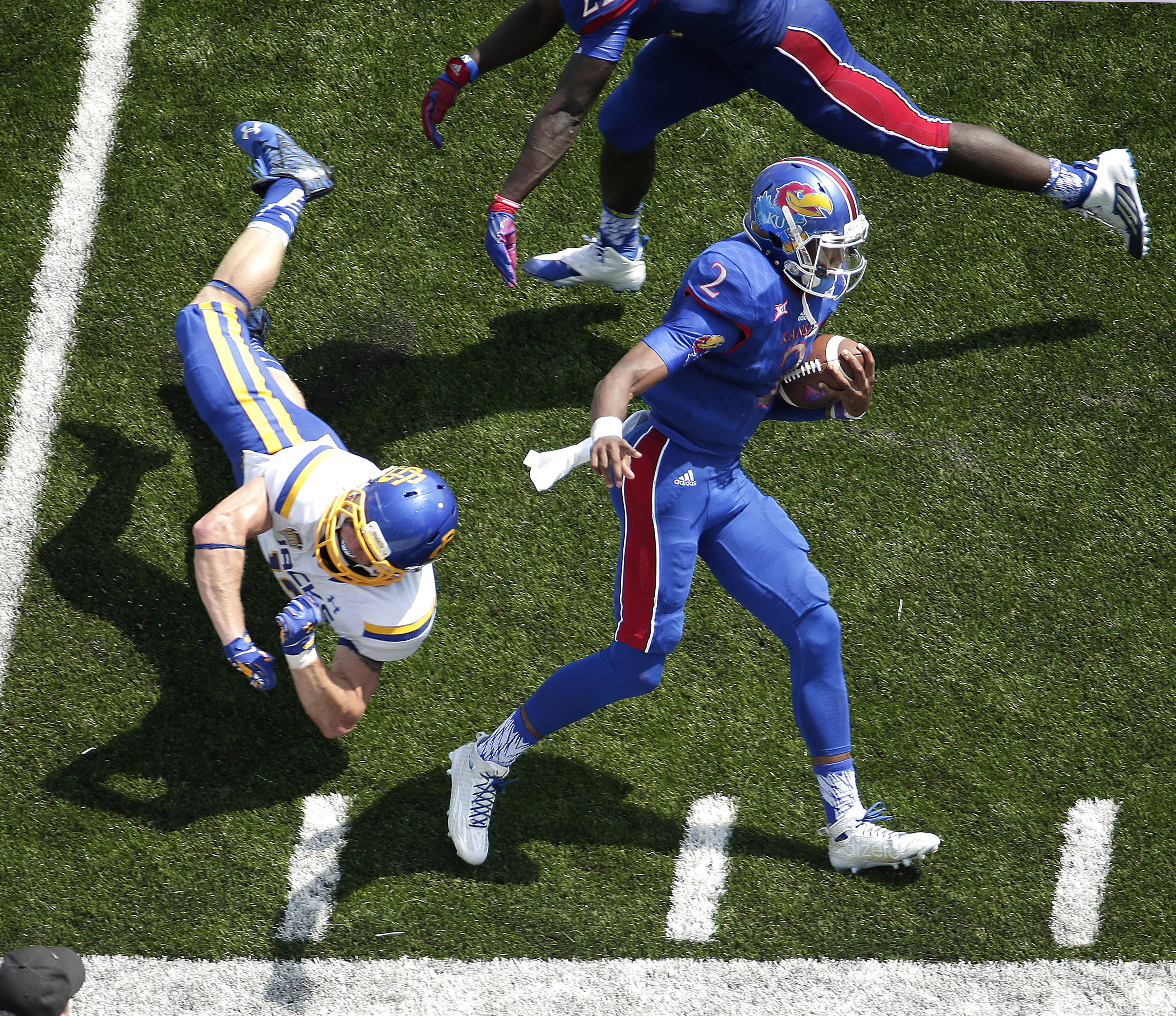 Kansas quarterback Montell Cozart (2) gets by South Dakota State linebacker Cody Hazelett (12) as he runs the ball during the first half of an NCAA college football game Saturday, Sept. 5, 2015, in Lawrence, Kan. (AP Photo/Charlie Riedel)