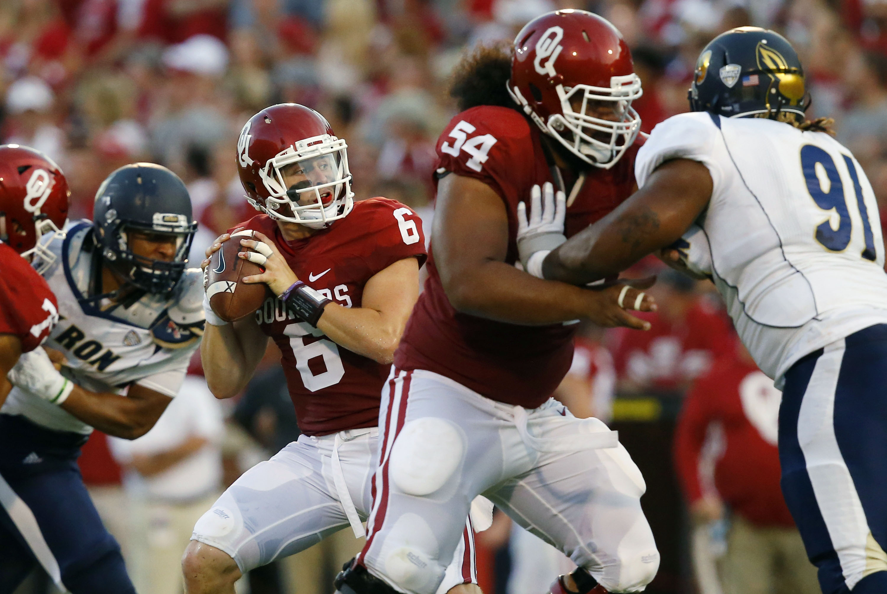 Oklahoma quarterback Baker Mayfield (6) passes under pressure in the second quarter of an NCAA college football game against Akron in Norman, Okla., Saturday, Sept. 5, 2015. At right are Oklahoma guard Nila Kasitati (54) and Akron defensive lineman Rodney