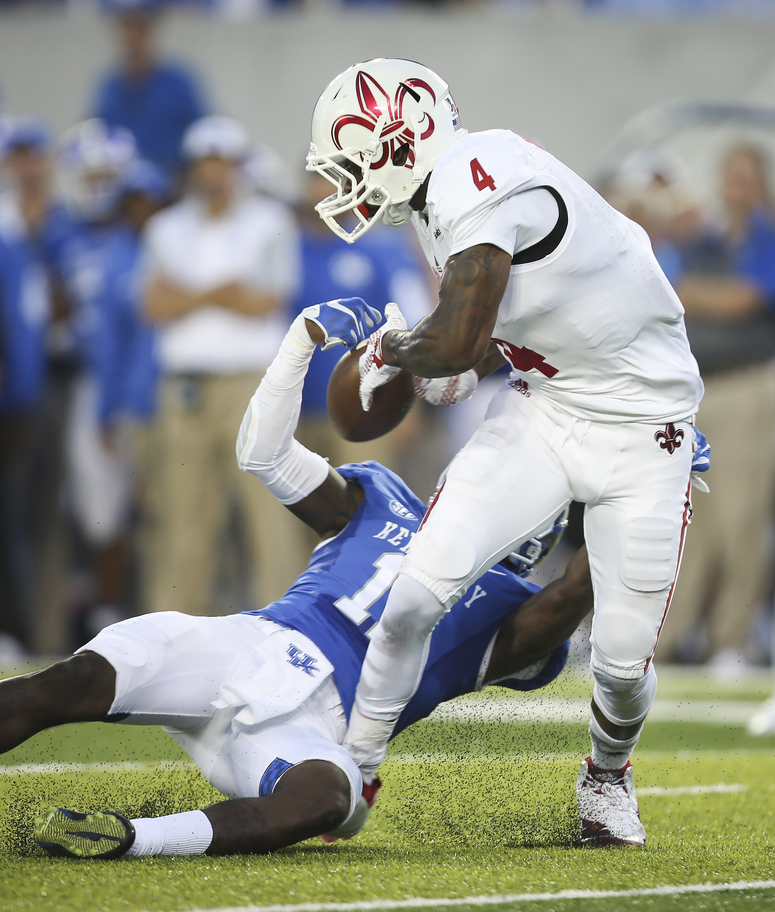 Louisiana-Lafayette wide receiver Jamal Robinson (4) has the ball stripped by Kentucky cornerback J.D. Harmon, which resulted in a turnover, during the first half of an NCAA college football game in Lexington, Ky., Saturday, Sept. 5, 2015. (AP Photo/David