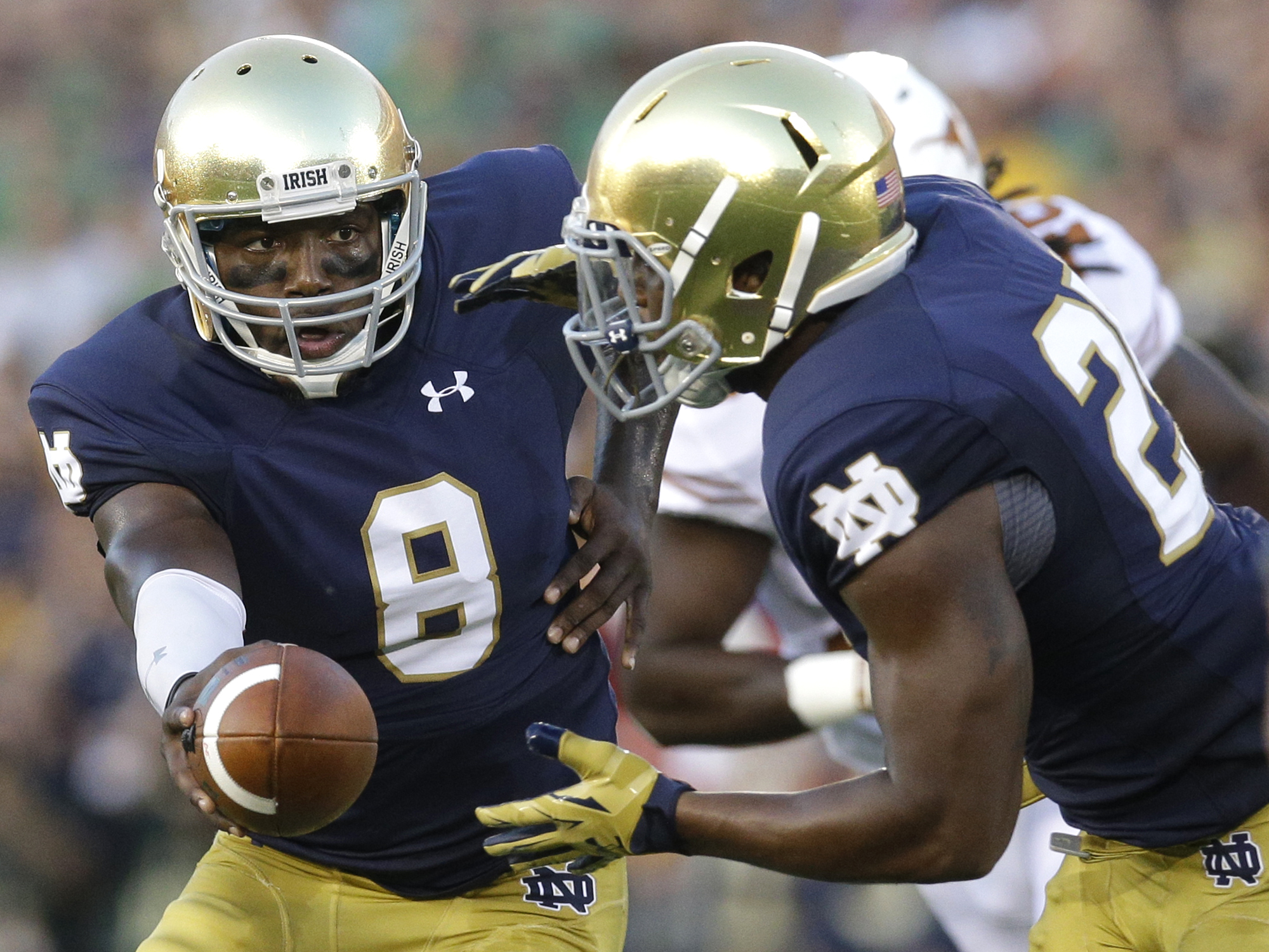 Notre Dame quarterback Malik Zaire, left, hands off to running back Tarean Folston during the first half of an NCAA college football game against Texas, Saturday, Sept. 5, 2015, in South Bend, Ind. (AP Photo/Nam Y. Huh)