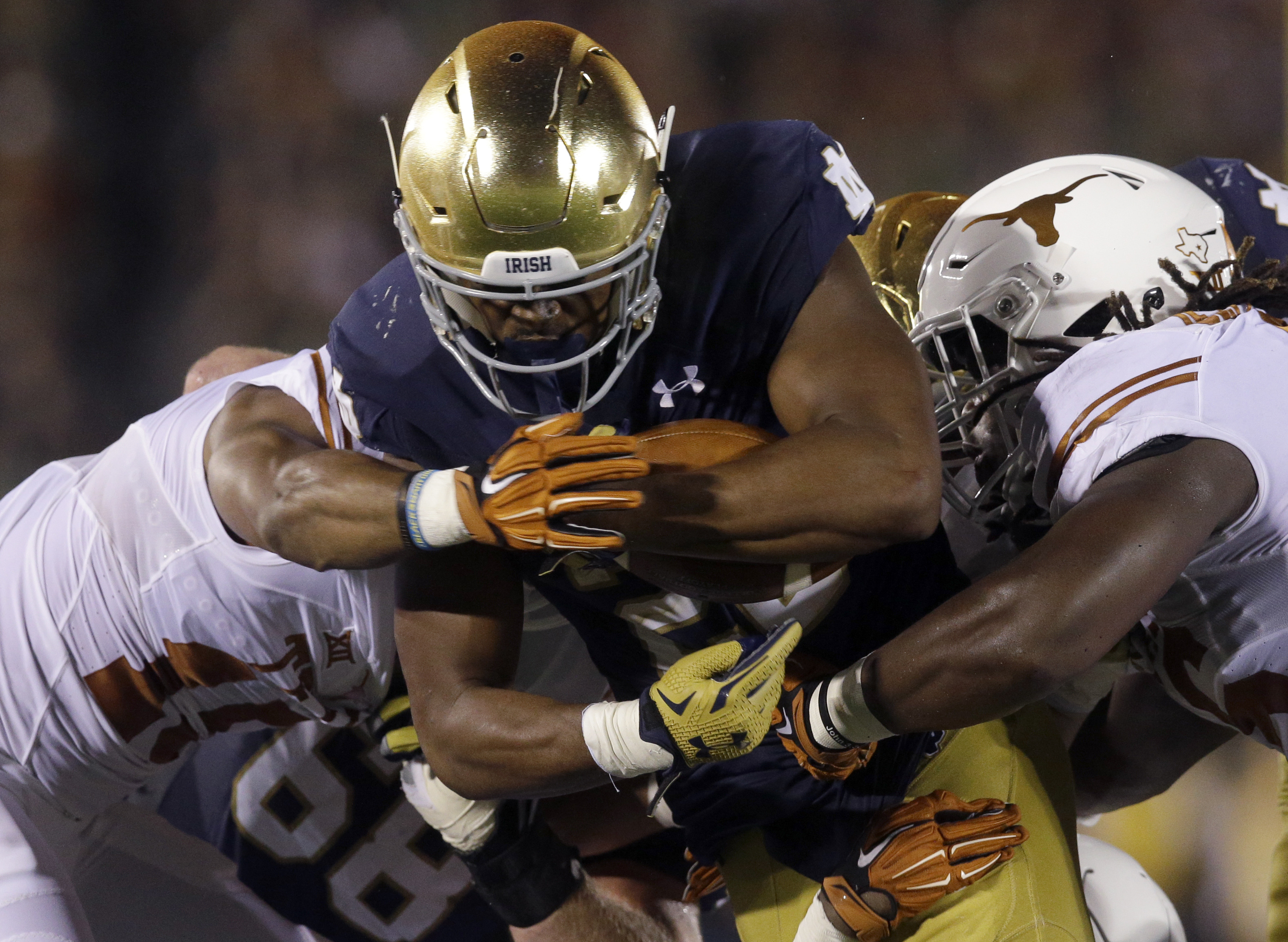 Notre Dame running back C.J. Prosise, center, runs with the ball against Texas cornerback Bryson Echols, left, and linebacker Malik Jefferson during the second half of an NCAA college football game Saturday, Sept. 5, 2015, in South Bend, Ind. Notre Dame w