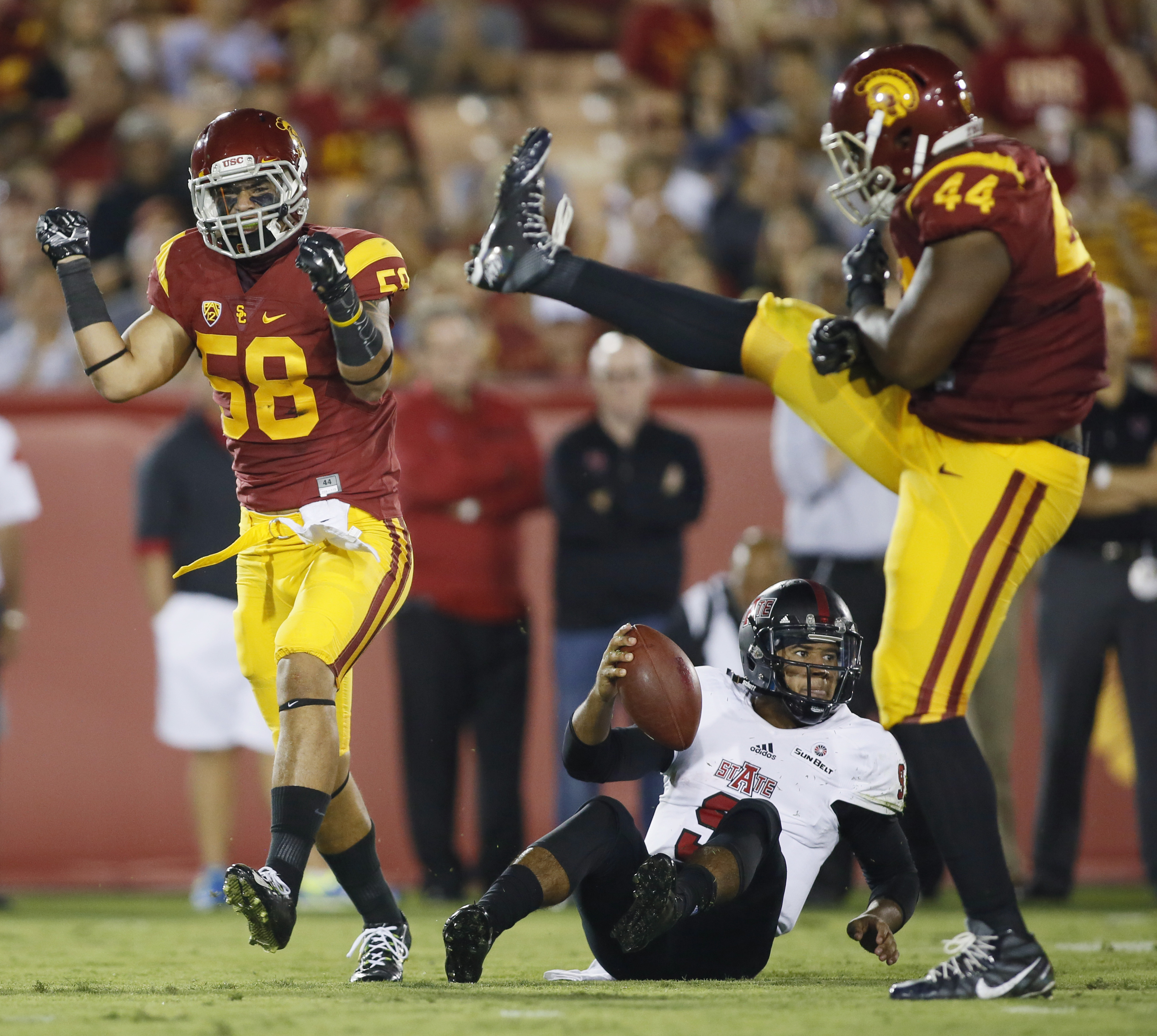 Southern California linebacker Osa Masina, left, celebrates sacking Arkansas State quarterback Fredi Knighten along with teammate Malik Dorton, right, during the first half of an NCAA college football game, Saturday, Sept. 5, 2015, in Los Angeles. (AP Pho