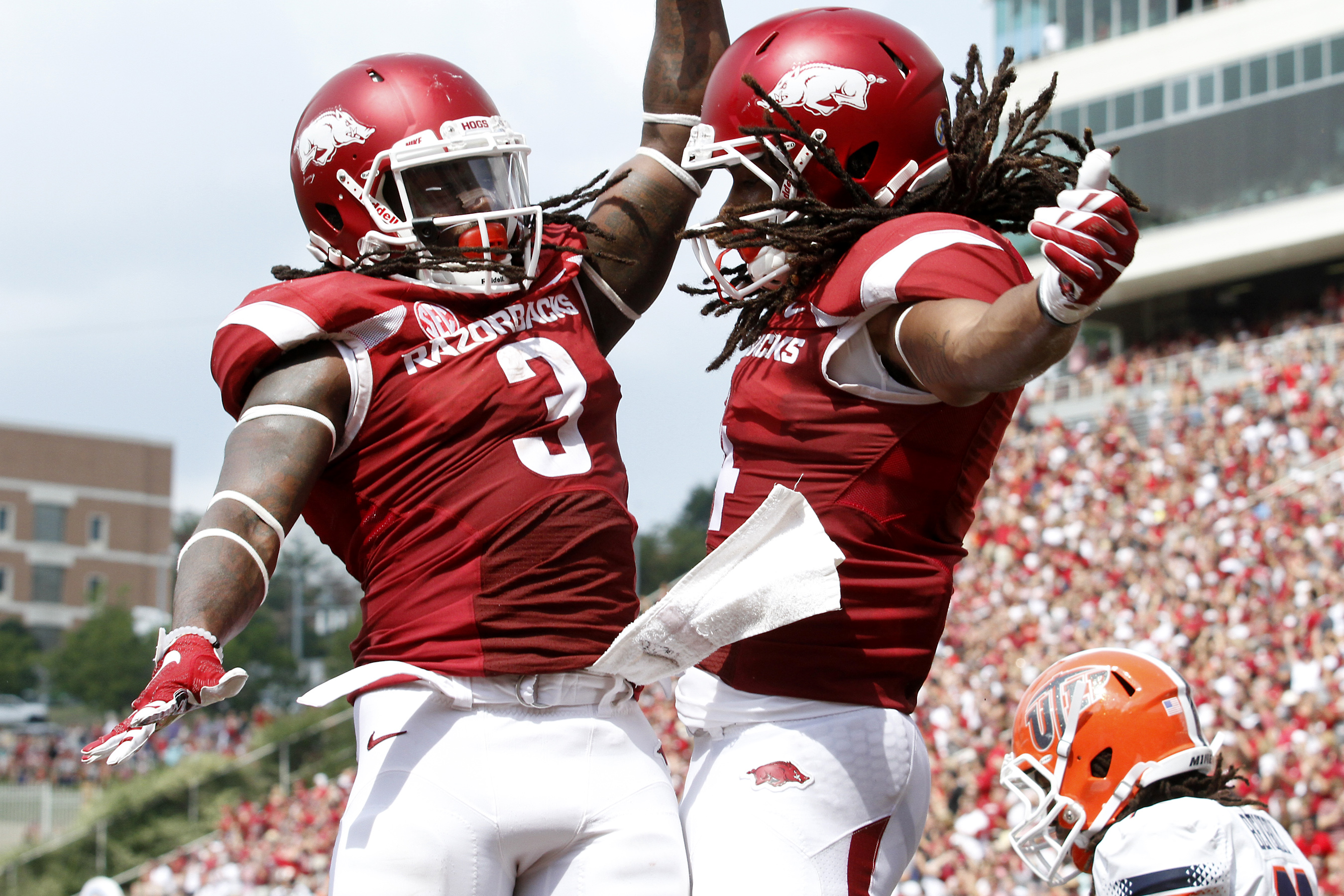 FILE - In this Sept. 5, 2015, file photo, Arkansas' Alex Collins (3) and Keon Hatcher (4) celebrate after Hatcher's touchdown during the NCAA college football game against UTEP at Donald W. Reynolds Razorback Stadium in Fayetteville, Ark. The Razorbacks b