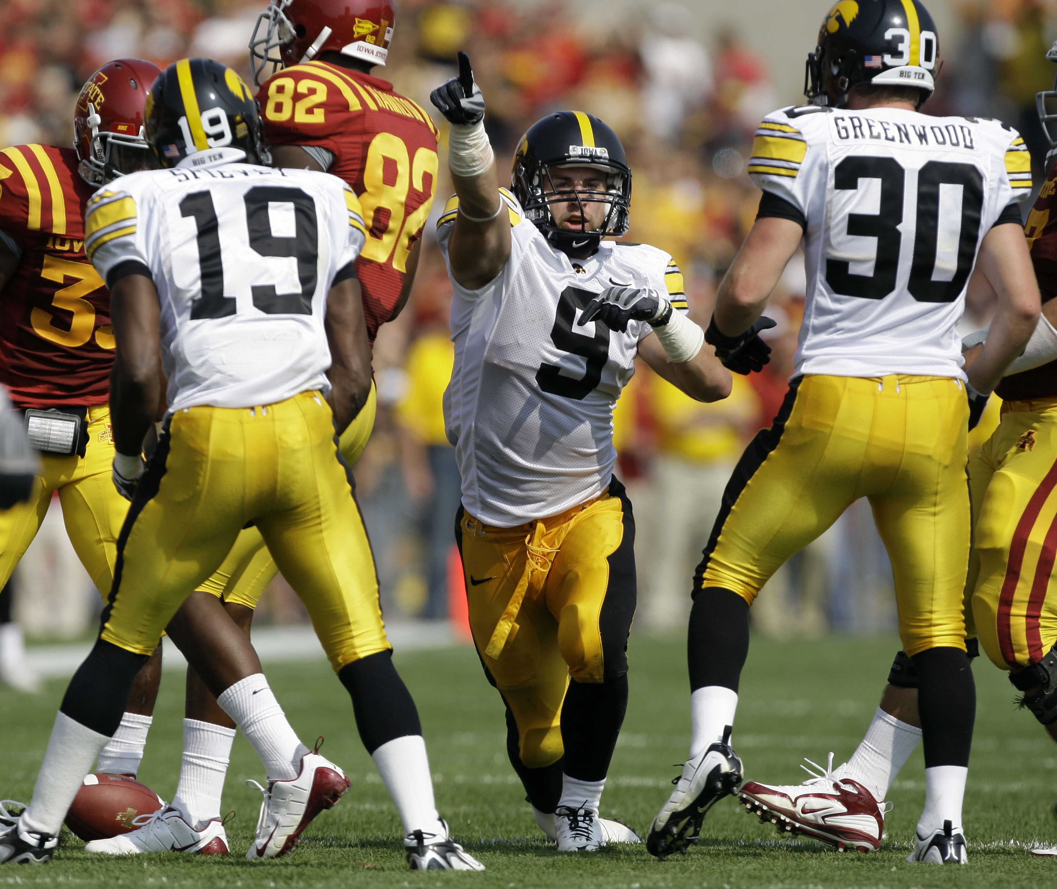 FILE - In this Sept. 12, 2009, file photo, Iowa's Tyler Sash (9) celebrates with teammates Amari Spievey (19) and Brett Greenwood (30) after intercepting a pass during the first half of an NCAA college football game against Iowa State in Ames, Iowa. Forme