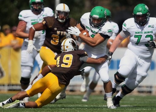 North Dakota running back Kyle Norberg is caught by Wyoming defensive back Anthony Makransky during an NCAA college football game Saturday, Sept. 5, 2015, in Laramie, Wyo. (AP Photo/Blaine McCartney)