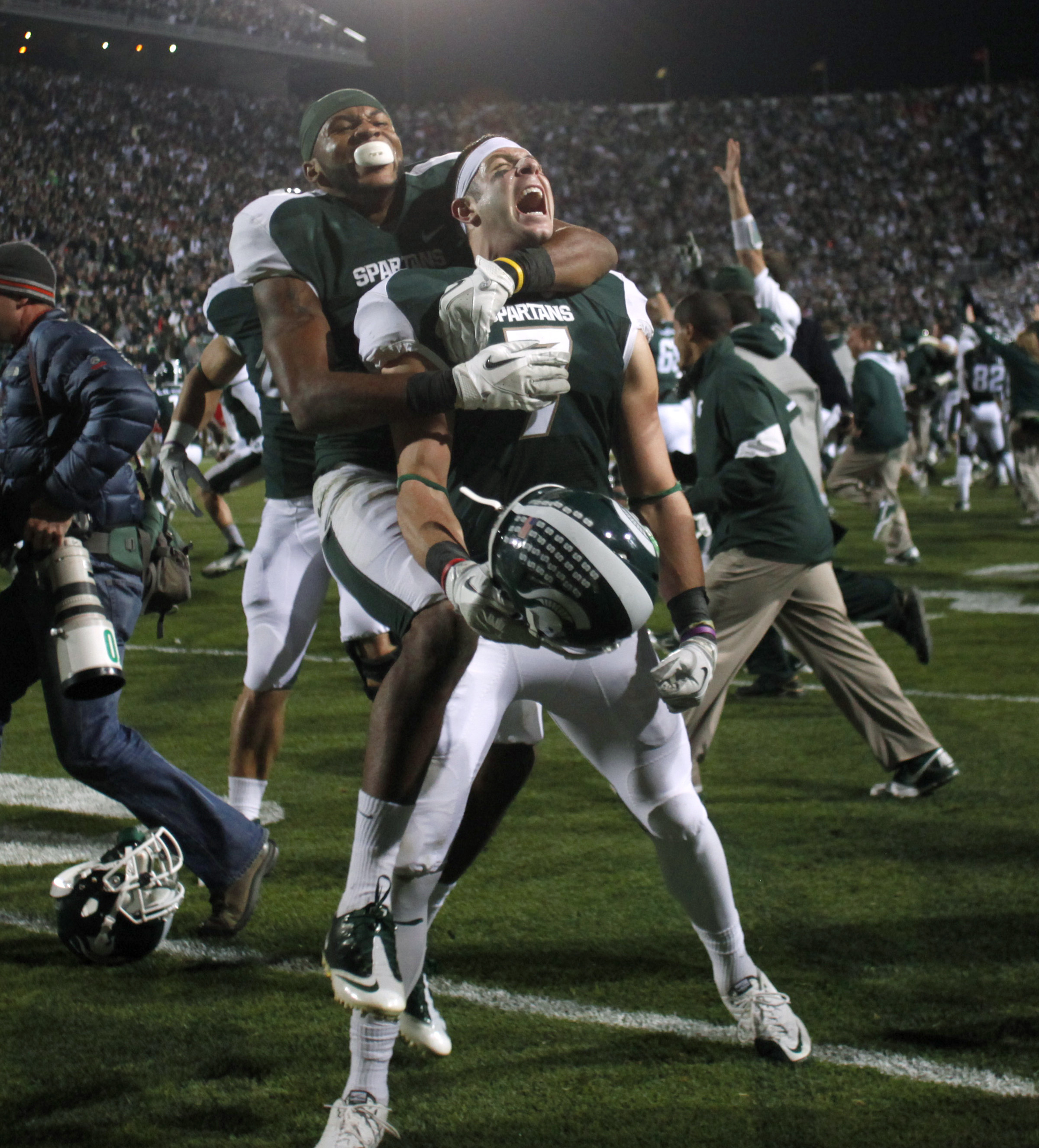 FILE - In this Oct. 22, 2011, file photo, Michigan State's Keith Nichol (7), center, and B.J. Cunningham celebrate following a 37-31 win over Wisconsin in an NCAA college football game in East Lansing, Mich. Nichol caught Kirk Cousins' 44-yarder for the t
