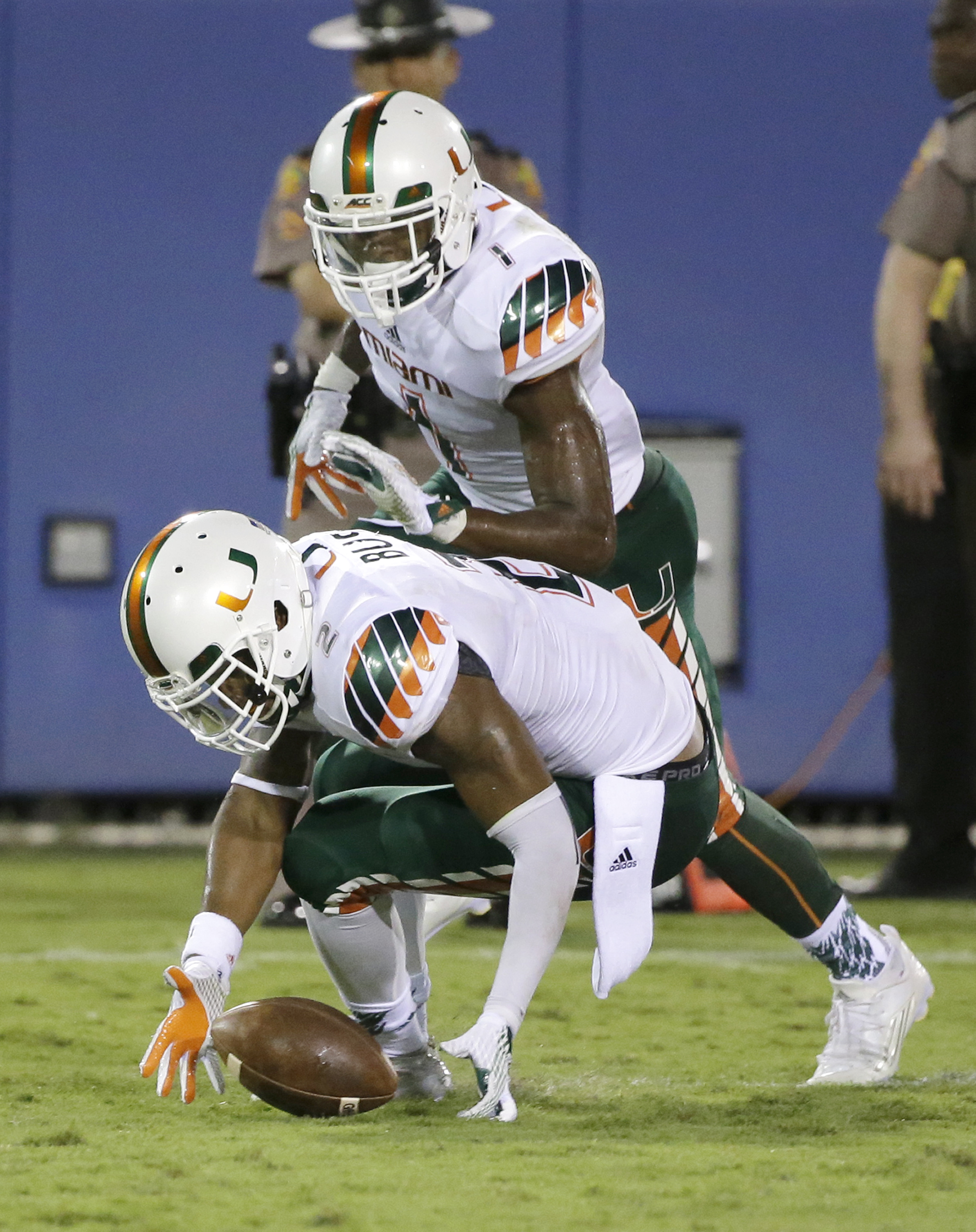 Miami defensive back Deon Bush, foreground, recovers a fumble by Florida Atlantic wide receiver Jenson Stoshak during the first half of an NCAA college football game, Friday, Sept. 11, 2015, in Boca Raton, Fla. Defensive back Artie Burns is at rear. (AP P