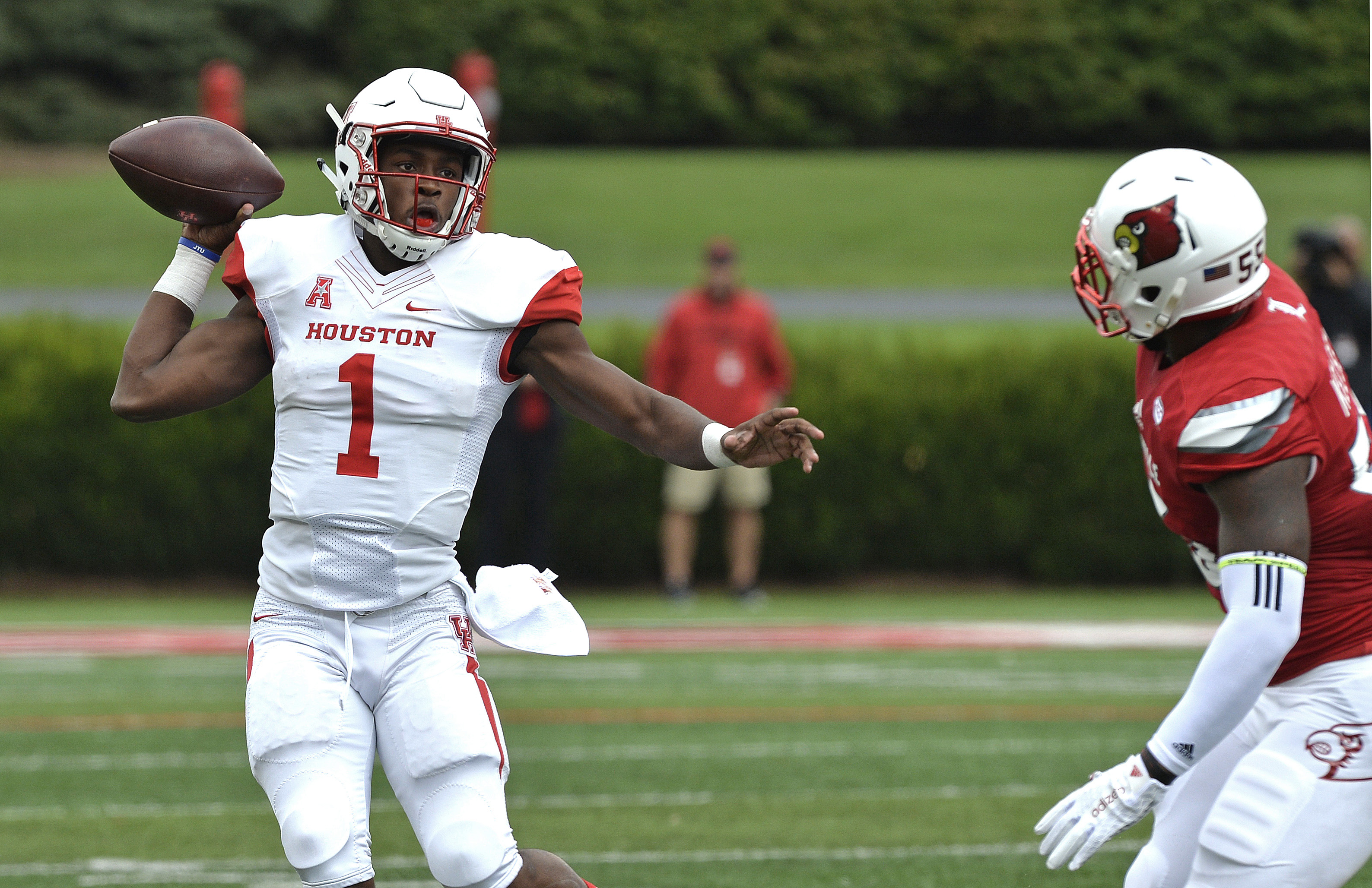 Houston's Greg Ward Jr. (1) attempts a pass away from the pursuit of Louisville's Keith Kelsey (55) during the first half of an NCAA college football game in Louisville, Ky. Saturday, Sept. 12, 2015. (AP Photo/Timothy D. Easley)