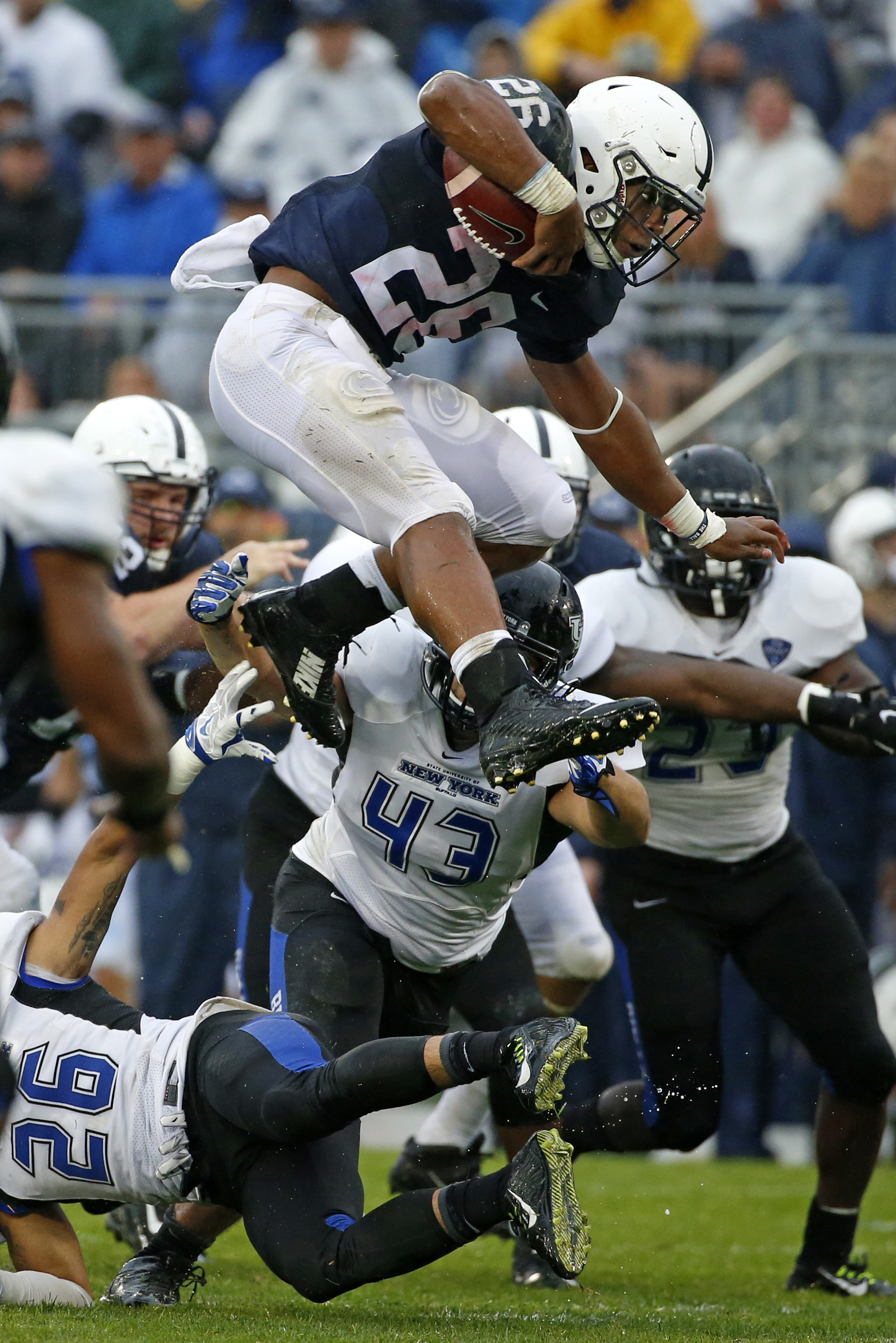 Penn State running back Saquon Barkley (26) leaps over Buffalo defenders safety Ryan Williamson (26) and linebacker Nick Gilbo (43) during the second half of an NCAA college football game in State College, Pa., Saturday, Sept. 12, 2015. (AP Photo/Gene J.